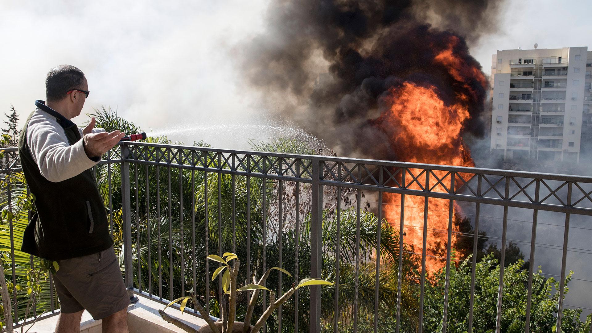 Un residente trata de proteger su vivienda de las llamas que se aproximan (AFP)