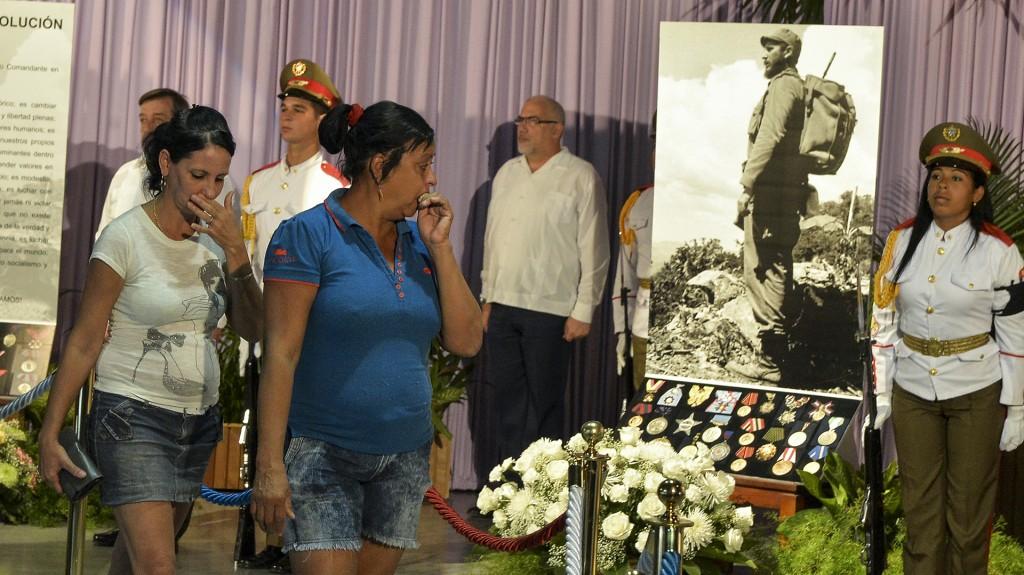 Asistentes al primer acto oficial por la muerte de Fidel Castro observan la imagen del líder revolucionario