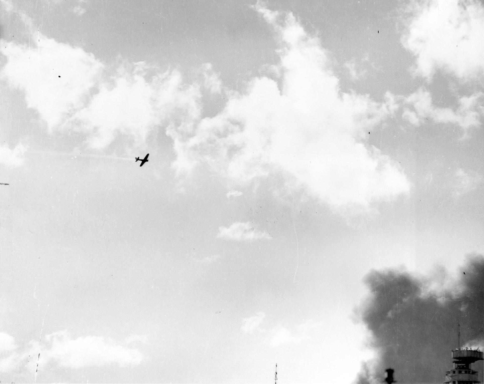 Una nave de combate japonesa tipo 00 despide estelas de humo tras ser alcnazada por fuego antiaéreo