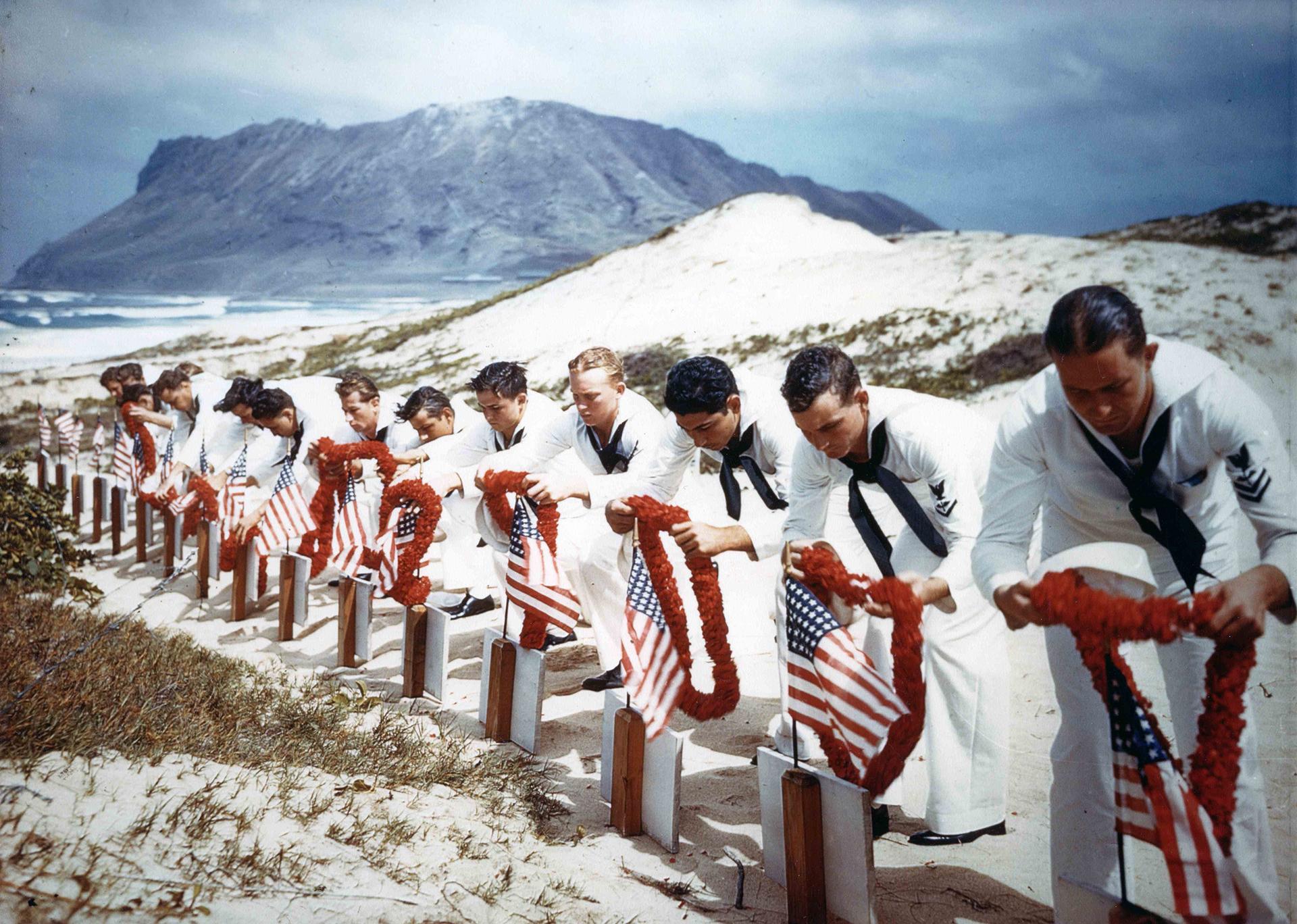Marineros decoran las tumbas de soldados caídos en la base aérea de Kaneohe, Hawai, poco después del bombardeo lanzado por Japón el 7 de diciembre de 1941. Se calcula que 2.400 estadounidenses murieron en el ataque japonés, y que supuso su entrada en la Segunda Guerra Mundial