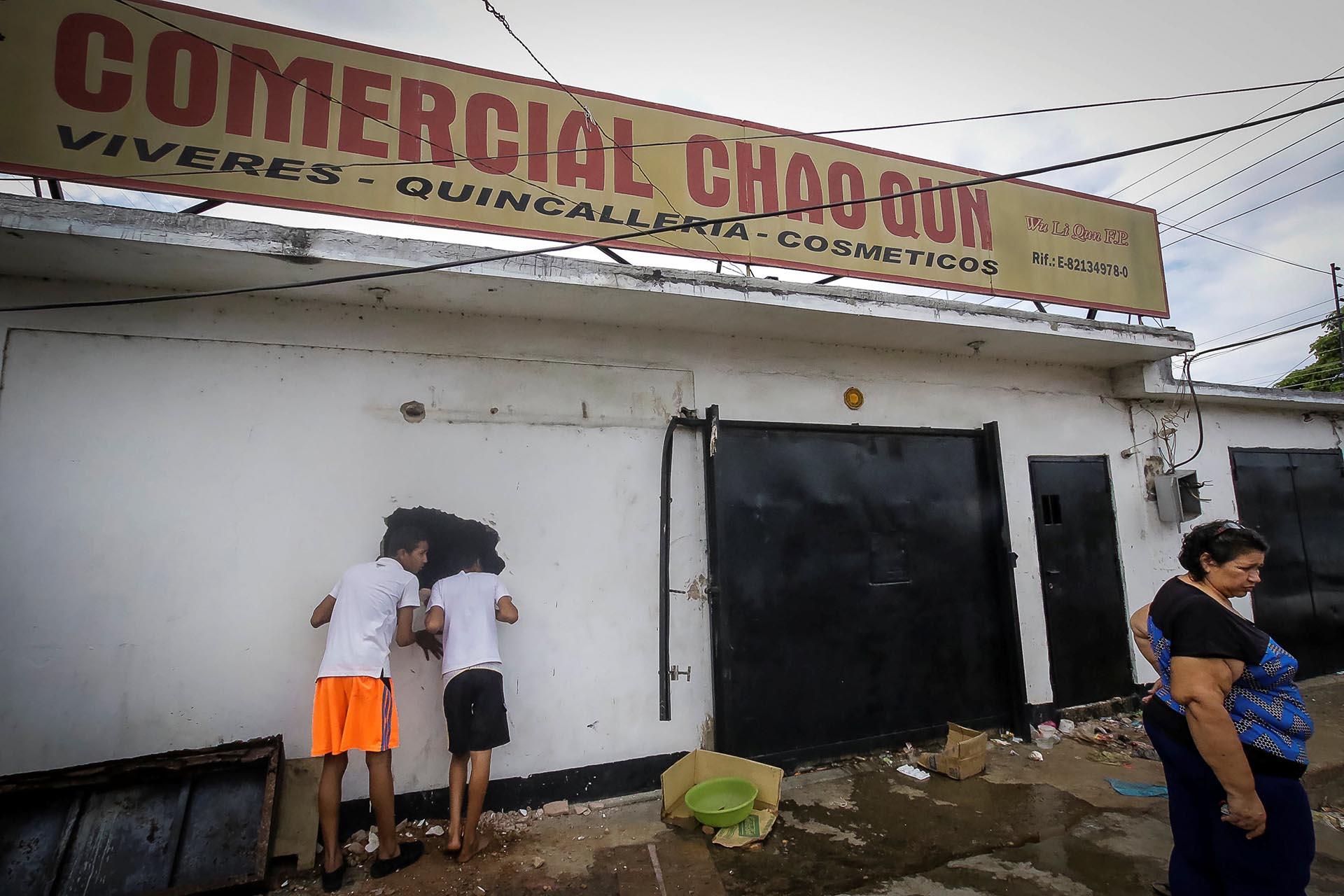 Jóvenes miran por el hueco en la pared de un supermercado saqueado en Ciudad Bolívar