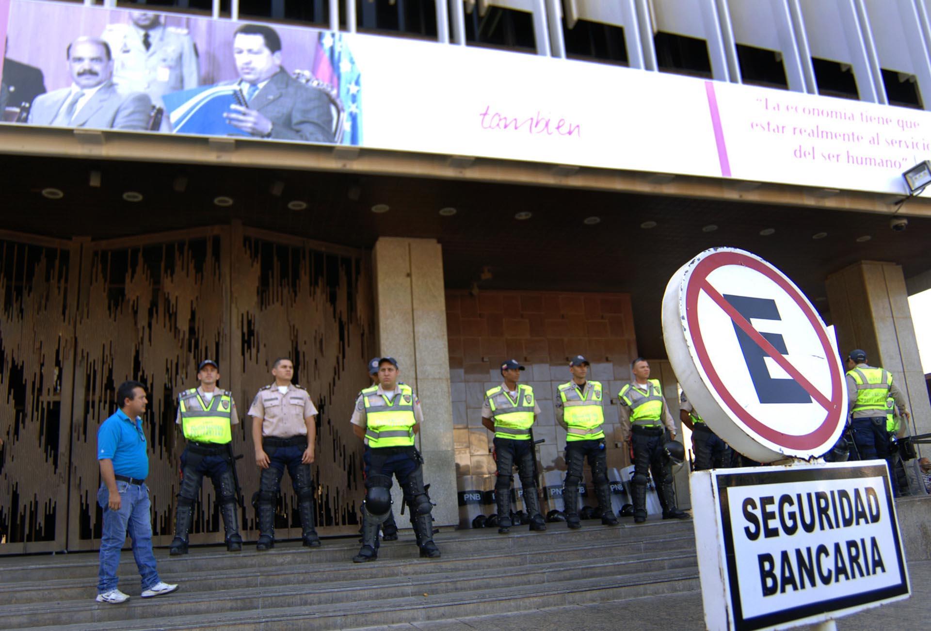 Personal de seguridad custodia la zona mientras un grupo de personas protesta en el centro y las inmediaciones del Banco Centra de Venezuela en Maracaibo