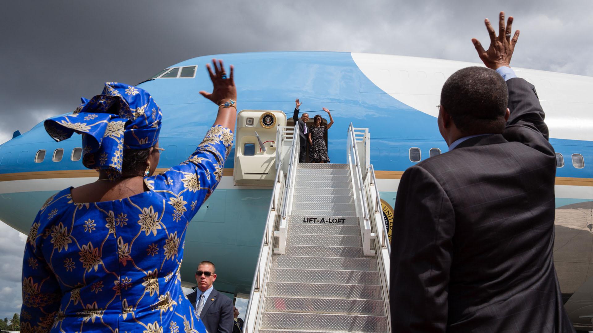 """El presidente Obama lanzó el programa """"Trade Africa"""" (Comercio con África) para impulsar los vínculos comerciales con África y dentro de África durante el viaje que realizó a tres países del continente en el verano de 2013. El presidente y la primera dama saludan al presidente Jakaya Kikwete de Tanzania y a su primera dama, Salma Kikwete, desde el avión presidencial Air Force One antes de partir de Dar es Salam, Tanzania. El presidente también visitó Sudáfrica y Senegal."""