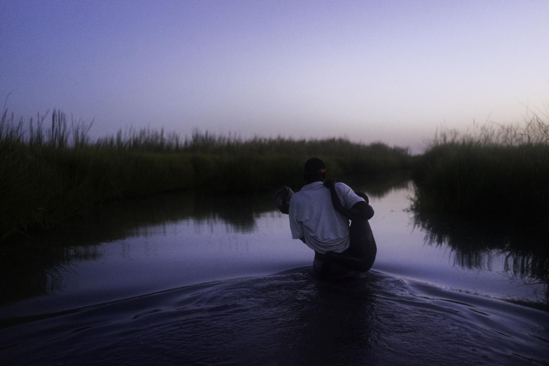 ISLA DE KOK, SUDÁN DEL SUR: Al atardecer, caminando a través de los pantanos del Estado de Unidad, un integrante de MSF carga a un niño mientras su familia se abre camino hacia la relativa seguridad de la isla de Kok, en donde más de 2000 personas se están refugiando del conflicto (©Dominic Nahr)