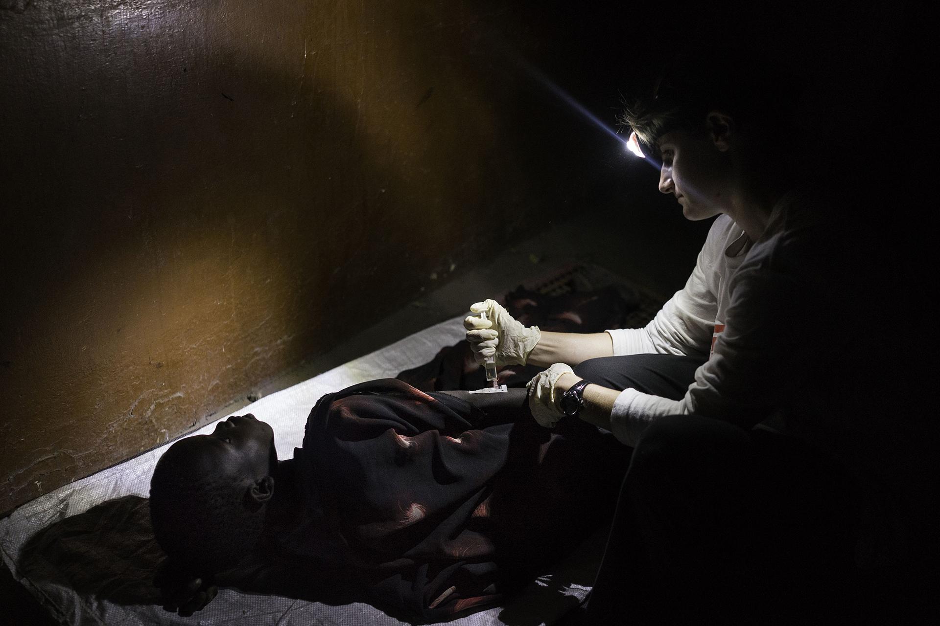LEER, SUDÁN DEL SUR: Un integrante de MSF monitoreando la condición de un niño bajo sospecha de padecer rabia, después de que un perro le mordiera la cabeza. Al ser forzado a evacuar el hospital de Leer después de que fuera atacado por hombres armados, el equipo de MSF está trabajando en un edificio abandonado. Si el niño da positivo en la prueba de rabia, será poco lo que el personal médico pueda hacer para salvarlo (© Dominic Nahr)