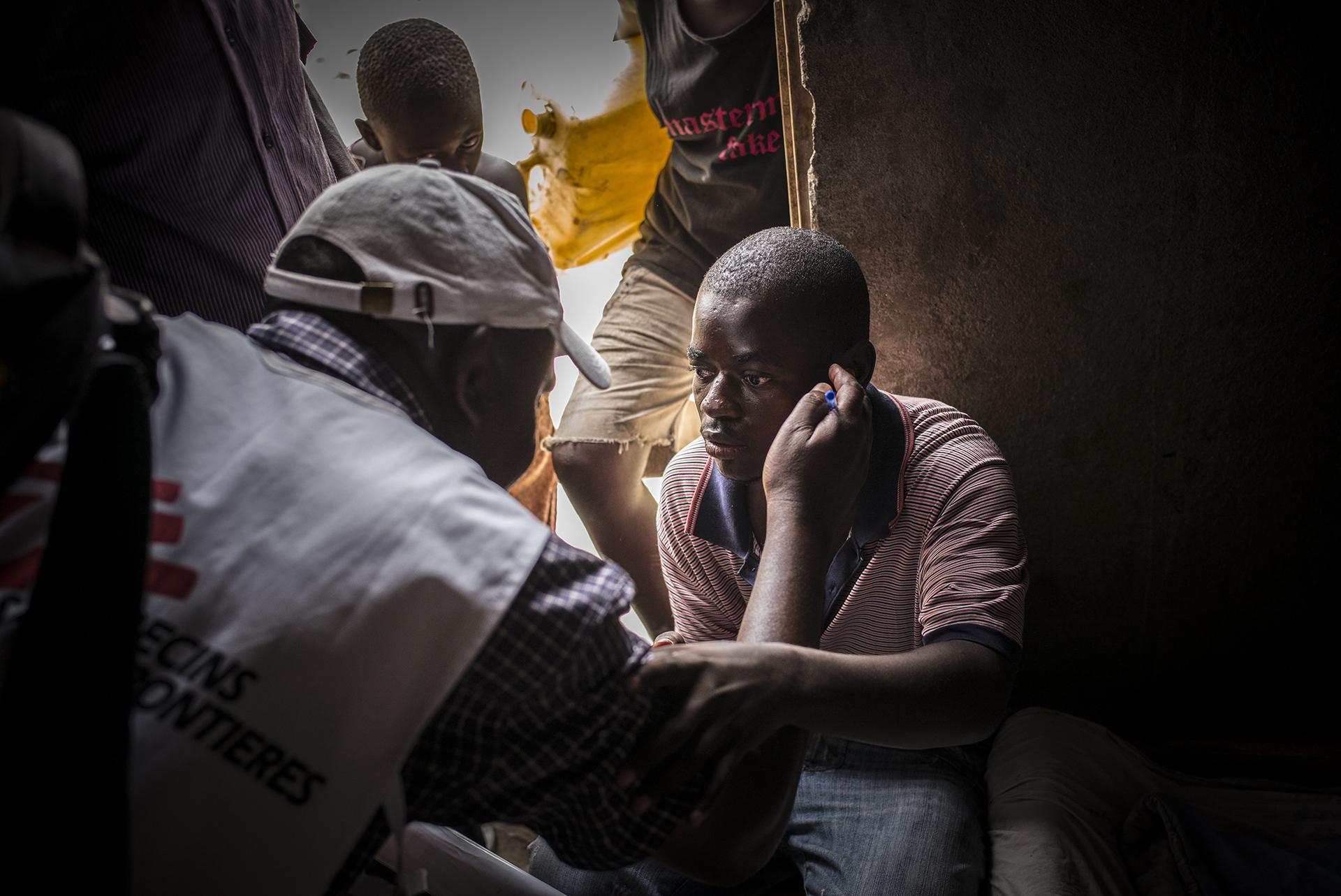 KATWE, UGANDA: Un trabajador de MSF hablando con un hombre con VIH positivo que perdió la vista y el oído cuando dejó de tomar sus medicamentos antirretrovirales a causa del estigma social. Los equipos de MSF pasan casa por casa a hacer pruebas de VIH en Katwe, Uganda (©Guillaume Binet/MYOP)