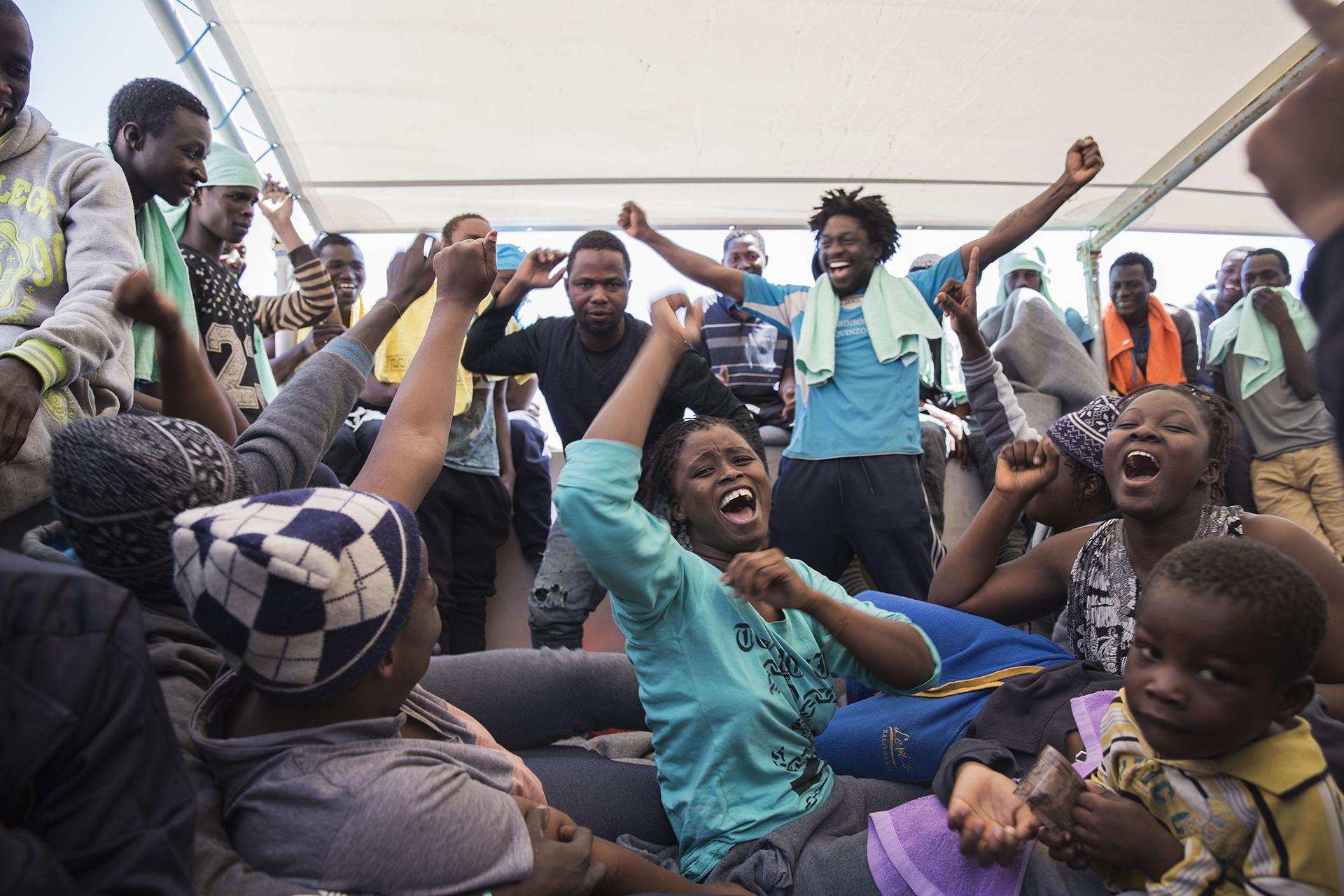 MAR MEDITERRÁNEO: A bordo del Dignity 1, un barco de búsqueda y rescate de MSF, un grupo de personas celebran haber sido rescatadas de un bote en peligro. Alrededor de 435 personas fueron salvadas, la mayoría eran de Guinea, Mali, Costa de Marfil y Senegal (© Anna Surinyach)