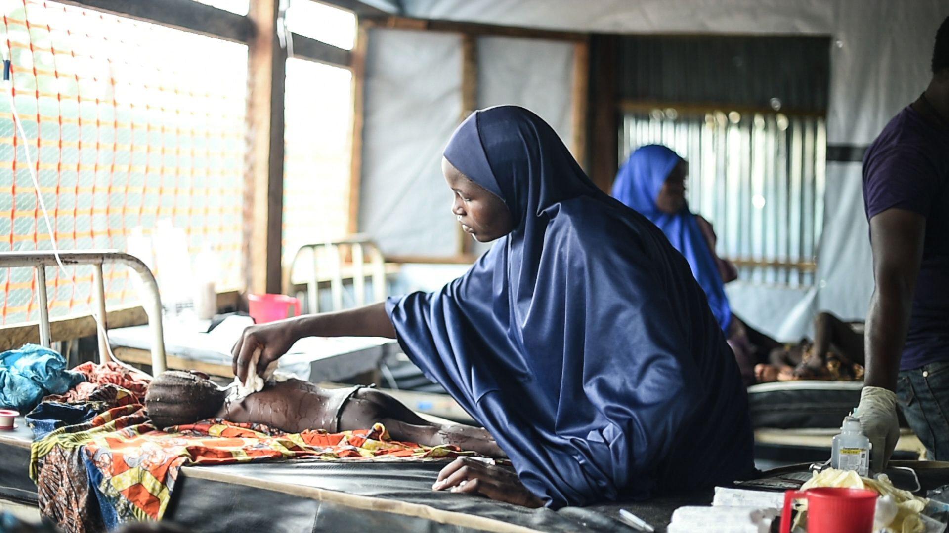 ESTADO DE BORNO, NIGERIA: Una madre colocando un trapo húmedo en el cuerpo de su hija para intentar bajar la fiebre en la sala de aislamiento del hospital general en Damboa, en el estado de Borno, en Nigeria. Su hija está siendo atendida por un sarampión con complicaciones. Los casos más severos son referidos al hospital en Biu, a dos horas de camino en auto (©Ikram N'gadi)
