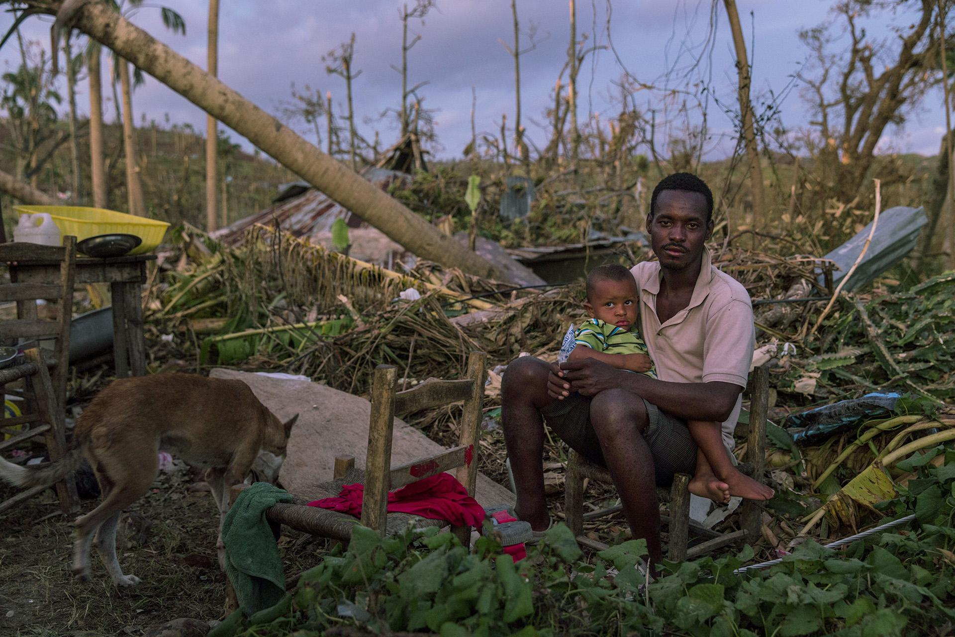 PORT SALUT, HAITÍ: Un hombre sentado junto a su hijo en lo que quedó de su hogar cerca de Port-Salut, en el sureste de Haití. El huracán Matthew arrasó en el Caribe el 4 de octubre, devastando grandes partes de la isla (©Andrew McConnell/Panos Pictures)