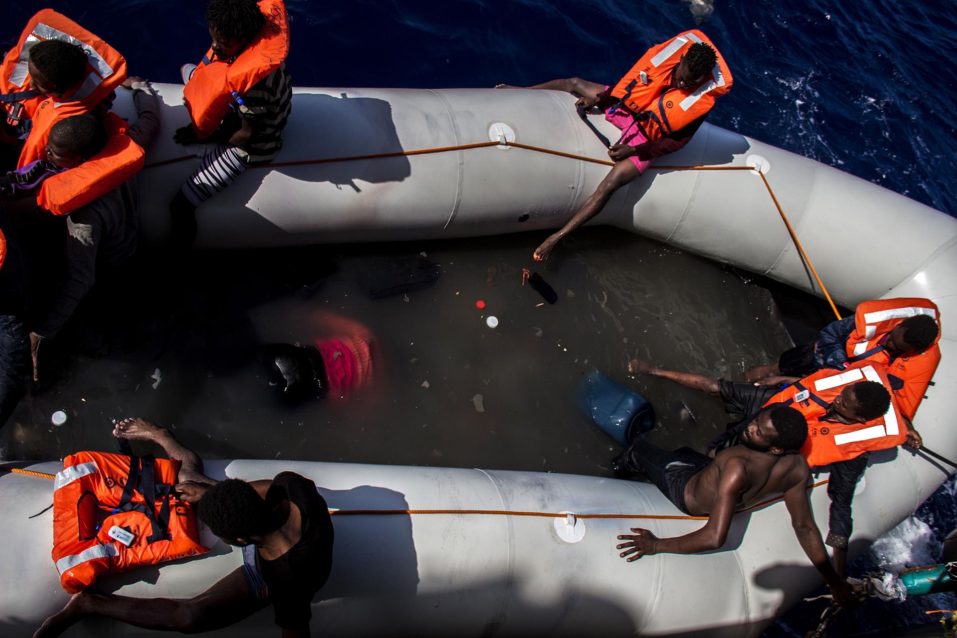 BÚSQUEDA Y RESCATE EN EL MEDITERRÁNEO: Un grupo de personas esperando ser rescatadas de un bote; junto a ellos están los cuerpos de quienes murieron intentando cruzar el mar Mediterráneo. Los equipos de MSF salvaron a 246 personas y encontraron 25 cuerpos sin vida en el bote (© Borja Ruiz Rodriguez)