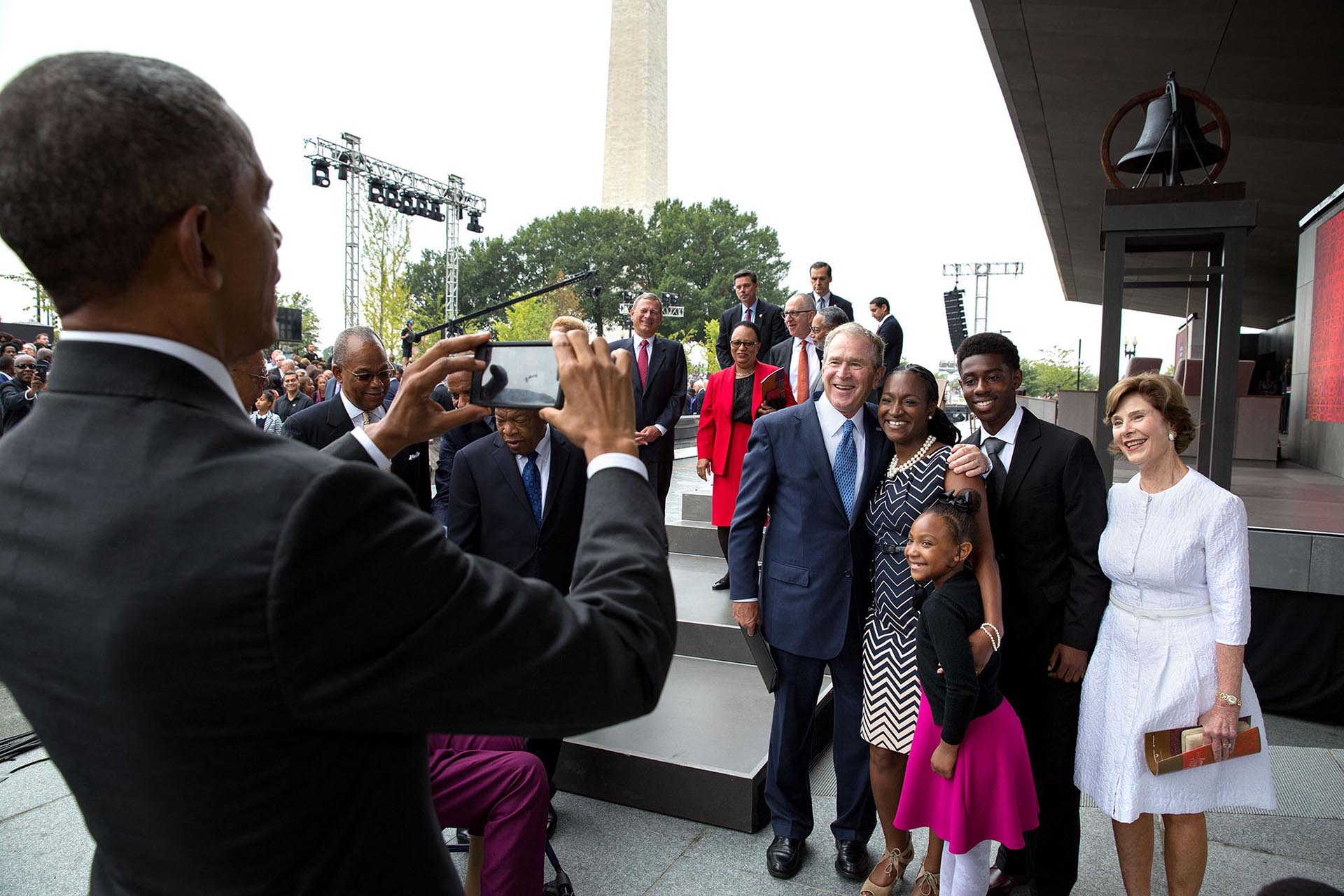 Obama, fotógrafo, retratando al ex presidente George W. Bush y su esposa junto a un grupo de personas que se acercaron a saludarlos