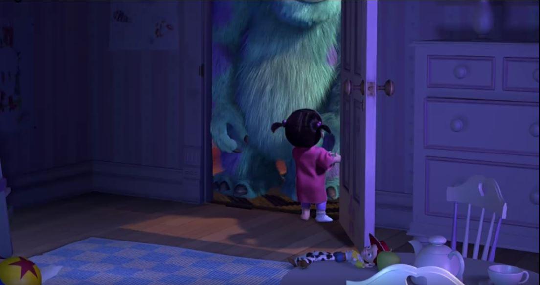 Boo dialoga con Sullivan en Monsters Inc. Sobre una mesa, puede observarse a Jessie