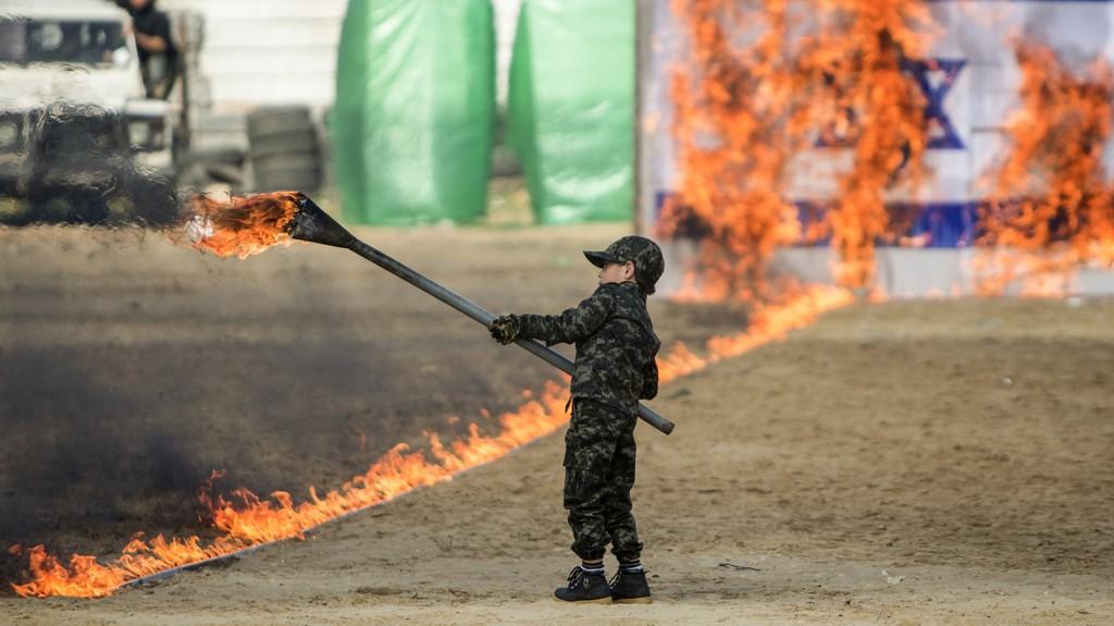 Un niño palestino enciende fuego a una bandera de Israel en el acto final del evento de graduación (AFP)