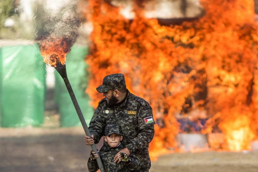 Un hombre ayuda al niño que prenderá fuego a la bandera de Israel durante la graduación (AFP)