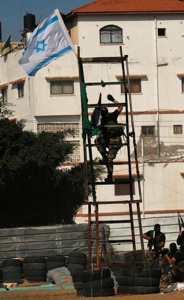 """Un miembro de Hamas busca retirar la bandera de Israel y reemplazarla con la de Palestina, señal de la """"captura"""" de la posición del ejército israelí (AFP)"""