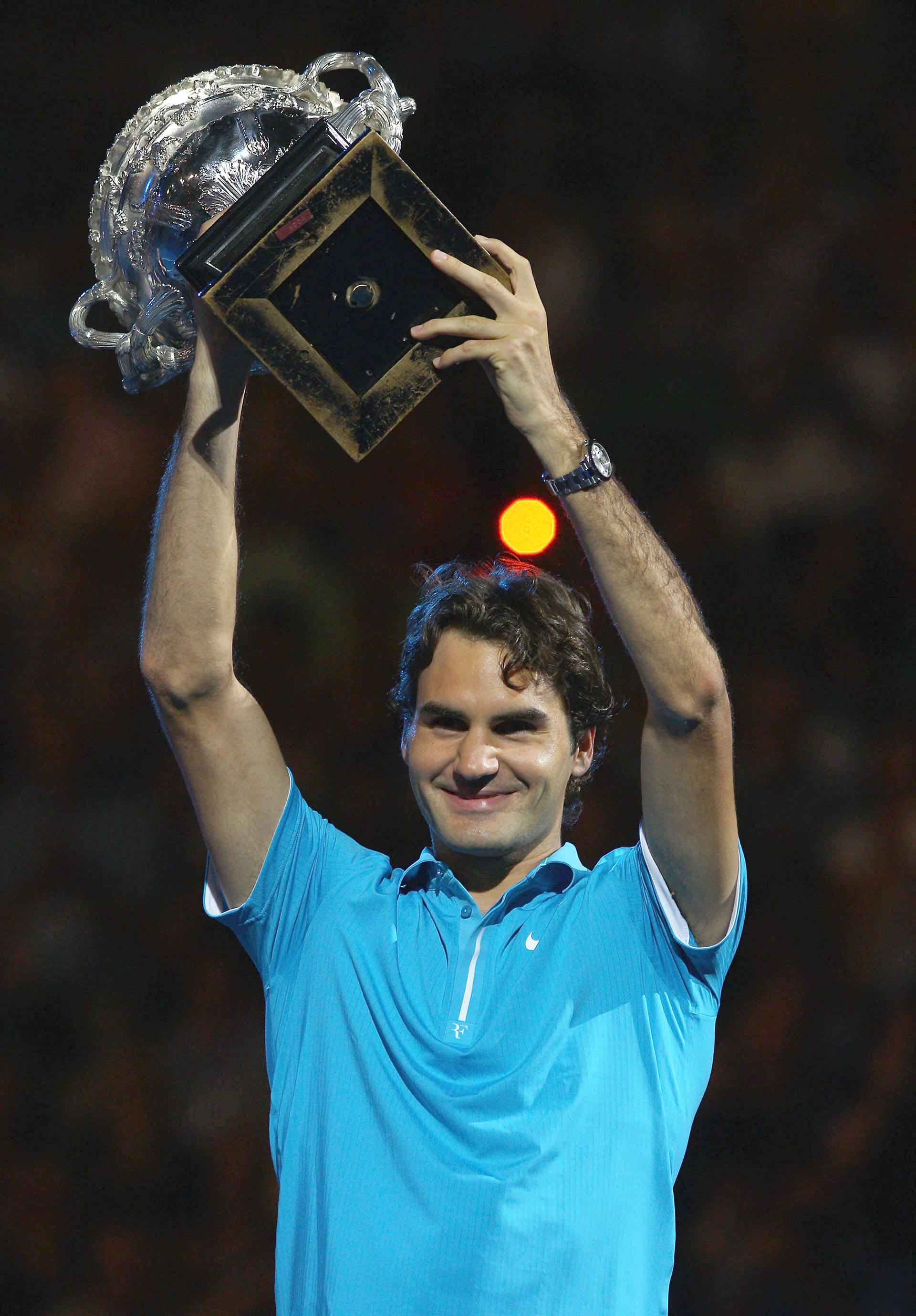 Roger Federer sostiene en alto la copa del desafío de Norman Brookes después de su emparejamiento final de los hombres contra Andy Murray, de Gran Bretaña