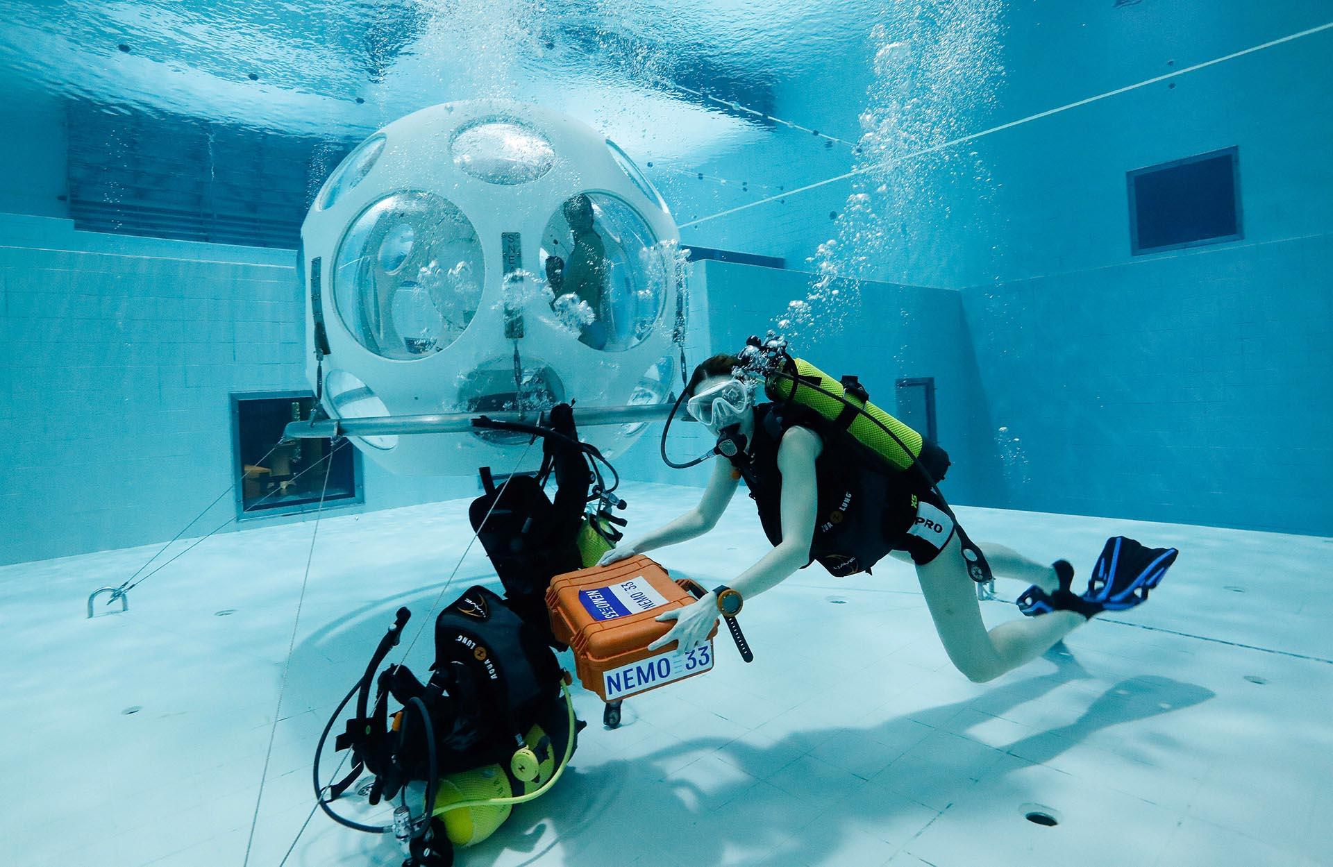 La mesera Valeryia Prusakova lleva uno de los pedidos en la caja hermética identificada con el nombre del centro de buceo, NEMO33 (REUTERS/Yves Herman)