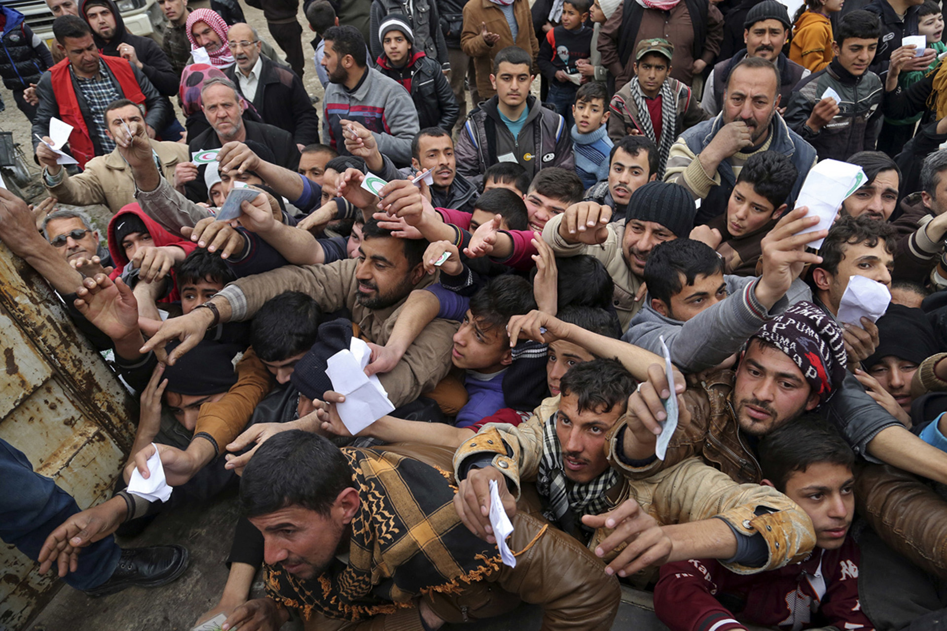 Habitantes de Mosul presentan sus tarjetas de racionamiento para recibir comida destribuida por la Media Luna Roja (AP)