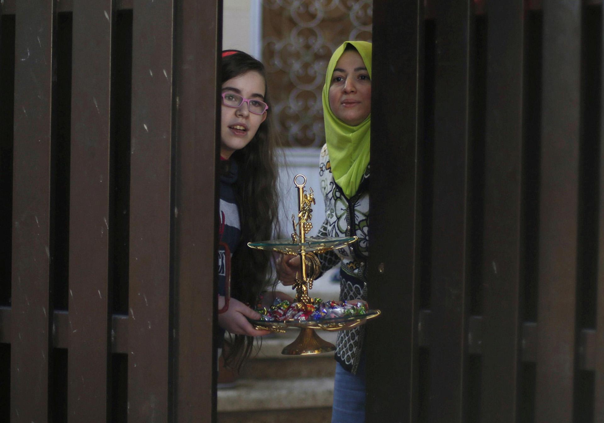 Civiles preparan dulces y golosinas para recibir a las fuerzas de seguridadque entran el distrito al Zirai(Reuters)