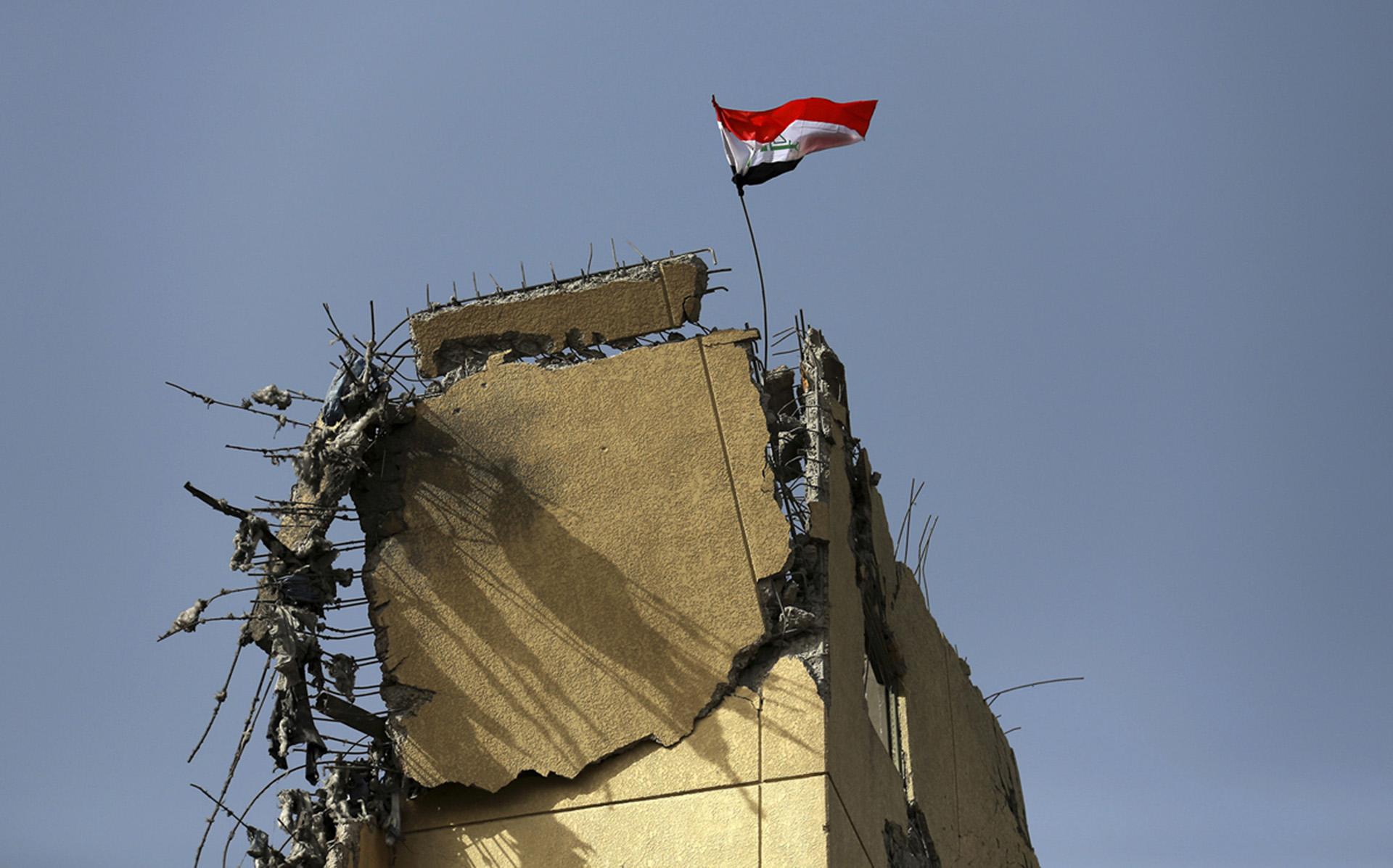 La bandera de Irak flamea sobre los restos del hospital al Salam, donde se libró la batalla más dura durante la recaptura del este de Mosul (AP)