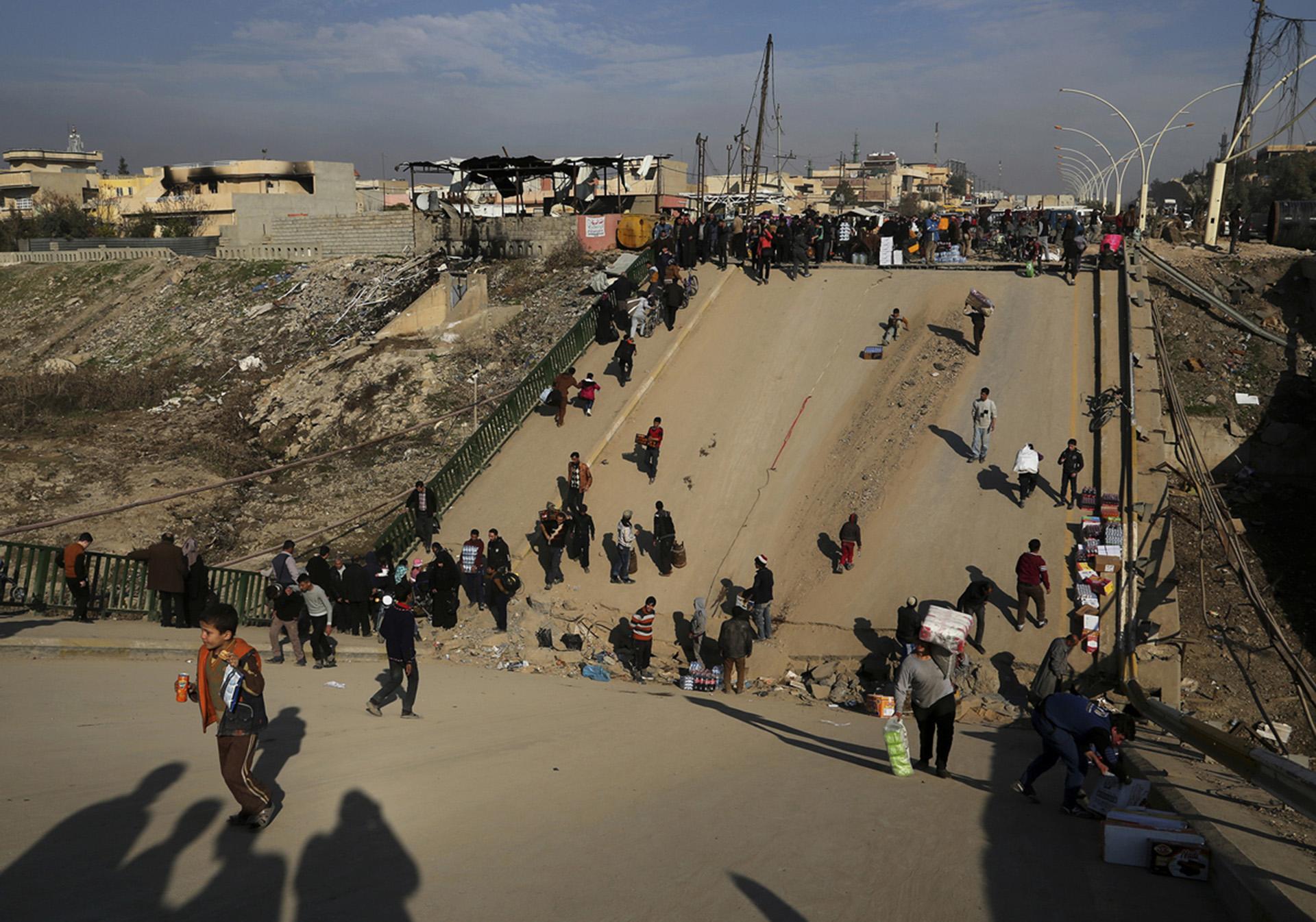 La gente cruza uno de los puentes que atraviesan el Tigris y que fueron destrozados por el ISIS (AP)