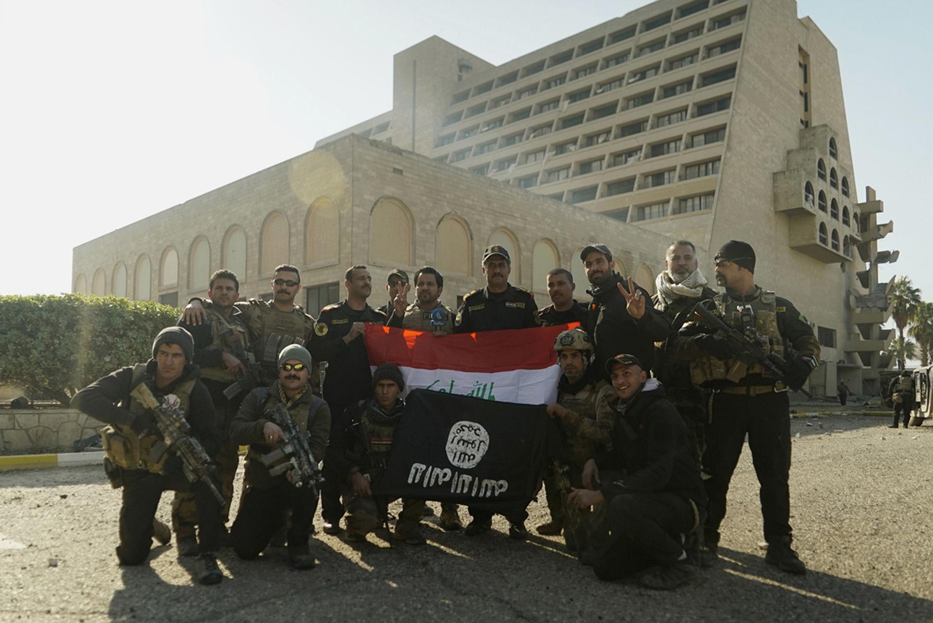 Tropas especiales posan con la bandera iraquí y una enseña del ISIS capturada, frente al Hotel Nineveh, otro objetivo preciado en esta primera parte de la ofensiva (AP)