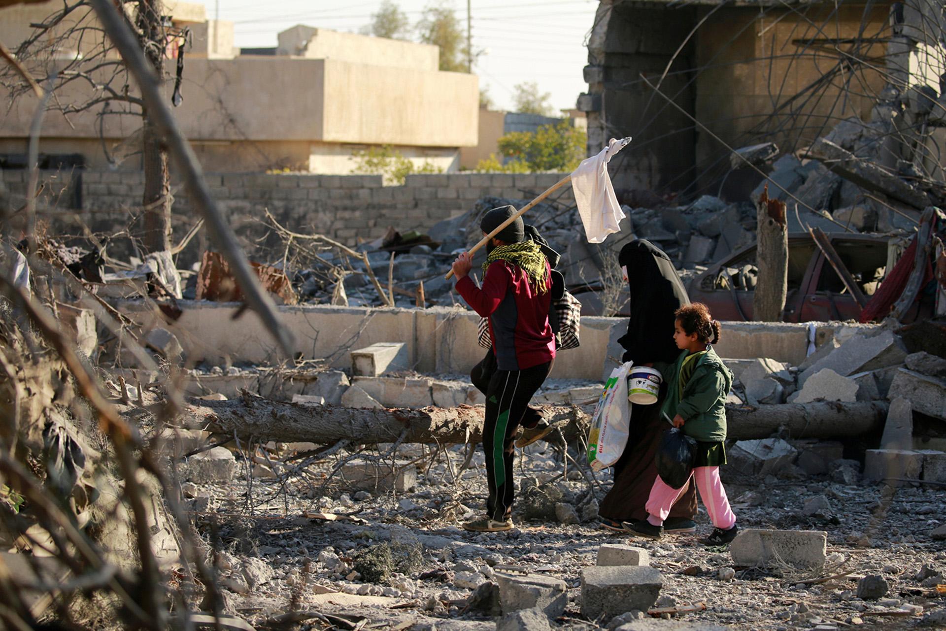 Civiles caminan con una bandera blanca en el distrito de Mithaq (Reuters)
