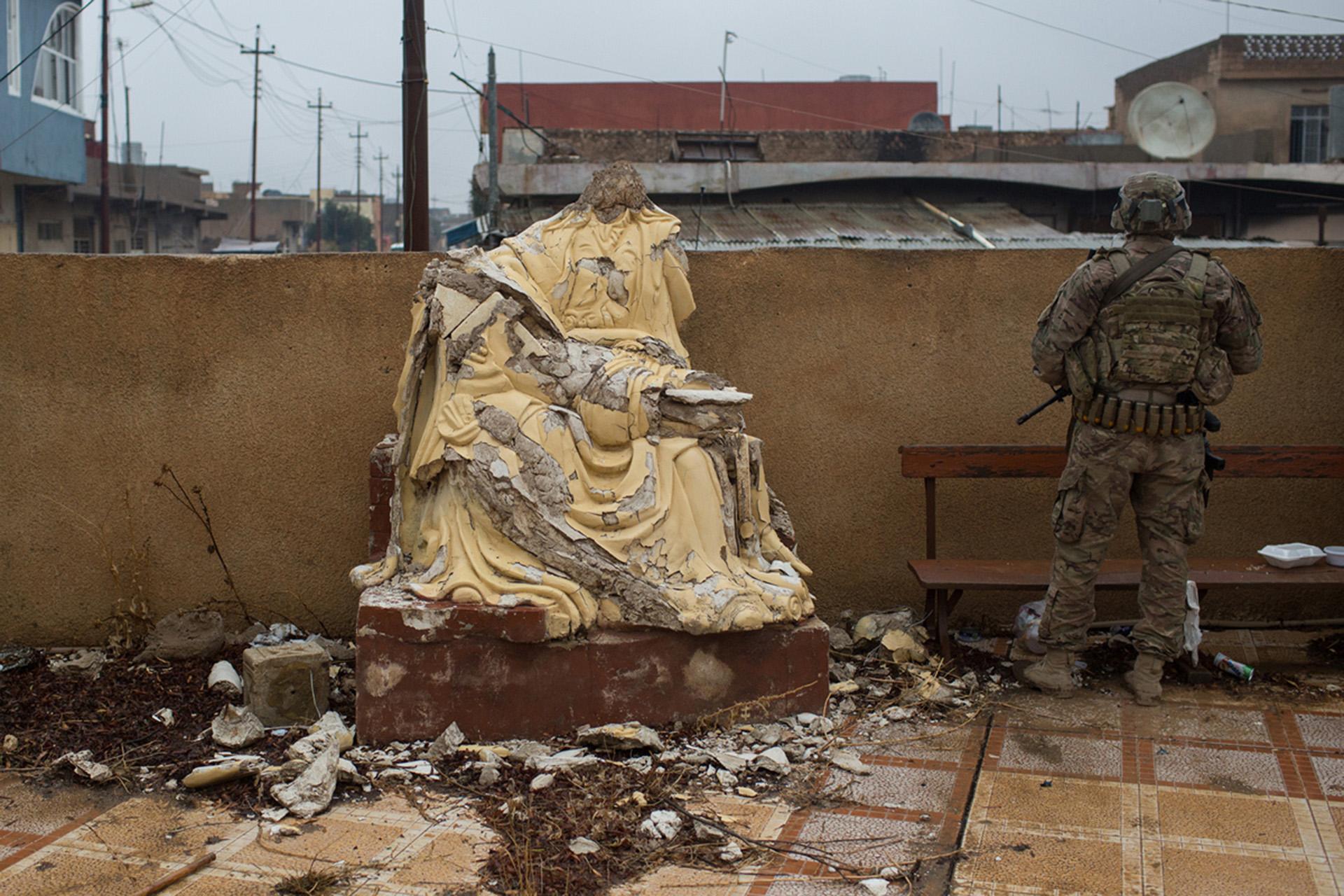Un soldado estadounidense junto a una estatua cristiana destruida. Bartella y Qaraqosh son dos pueblos cristianos en las afueras de Mosul recientemente liberados (Getty)