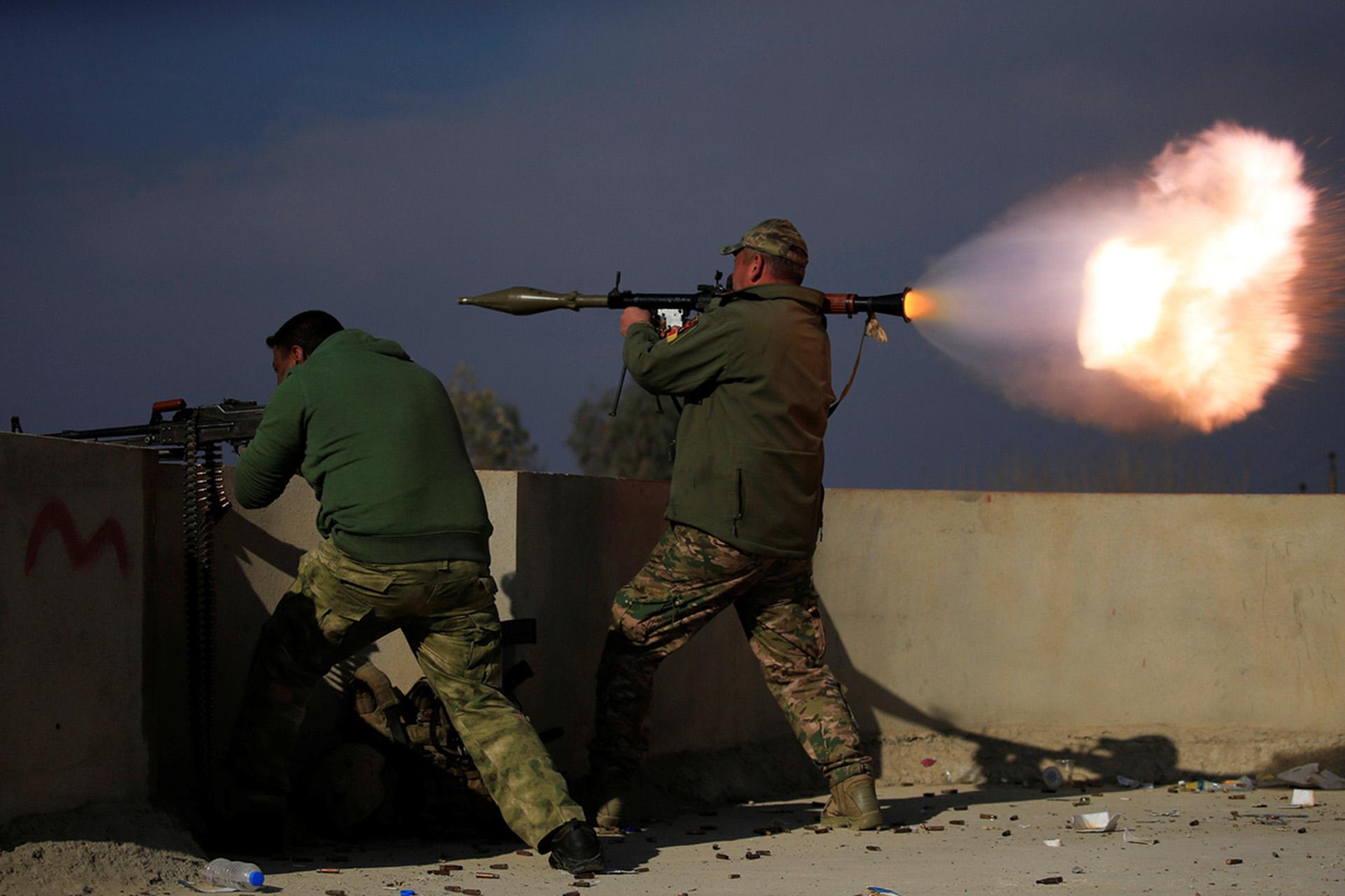 Un soldado iraquí dispara un misil RPG y otro opera una ametralladora desde el techo de ua casa en Mosul (Reuters)