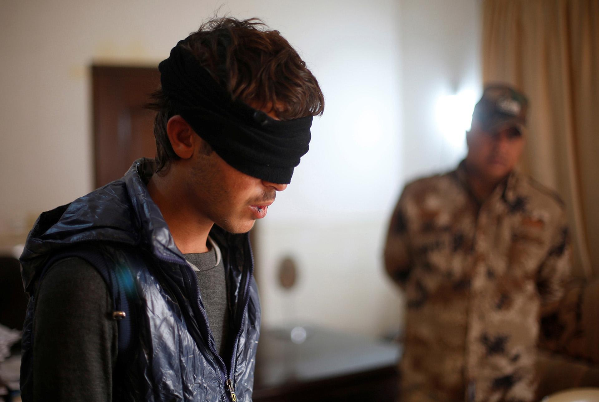 Un detenido, sospechoso de colaborar con ISIS, espera ser interrogado (Reuters)