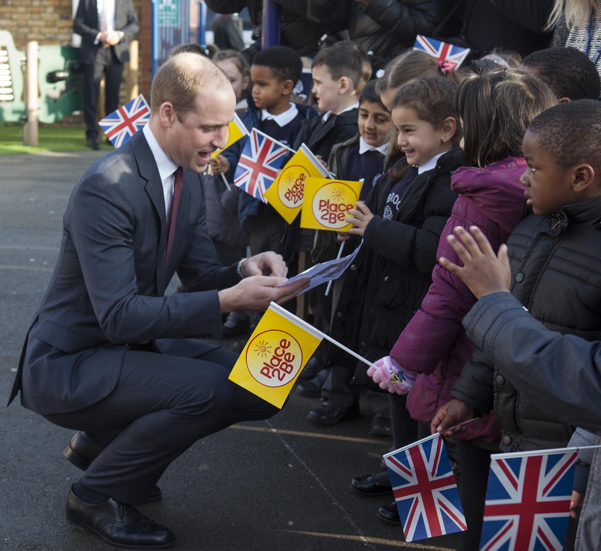 De elegante traje, el príncipe Guillermo también conversó con los chicos que los recibieron con banderas