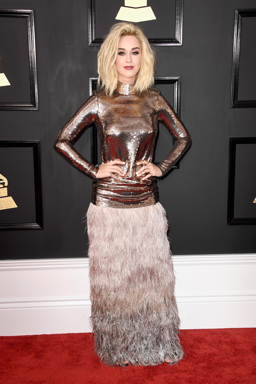 Katy Perry en 2017 lució un vestido con mix de tendencias: paillettes y plumas. El torso superior de mangas largas con cuello polera de paillettes en ocre y la falda de plumas en degradés plateados. De accesorios apostó a los mini anillos