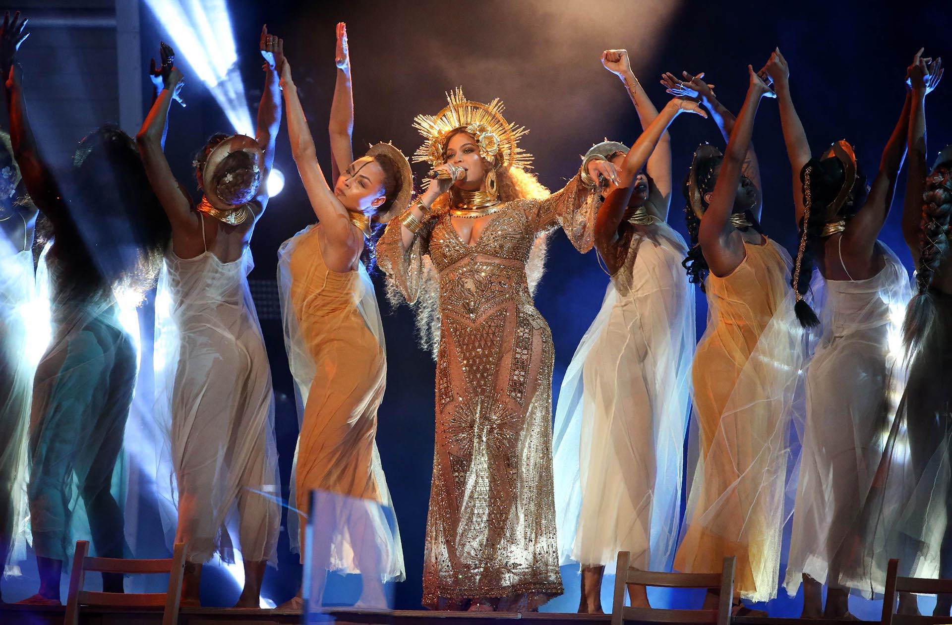Durante el show que brindó Beyoncé en los Grammy del 2017, la cantante lució un impactante vestido-joya íntegramente bordado con piedras, canutillos y mostacillas inspirados en el art decó, en dorado y plateado. Como detalle de lujo, la corona-tocado, los ganchos, la cogotera y los maxi aros todo en dorado