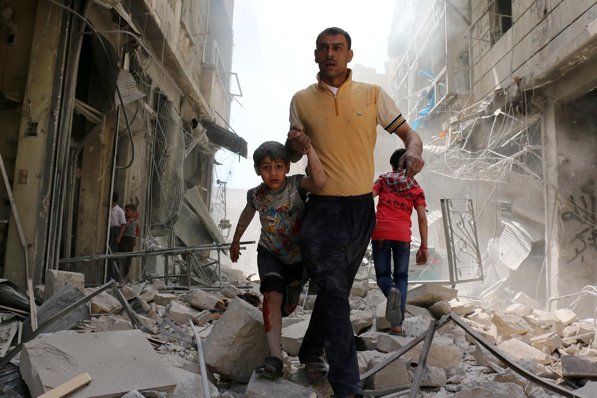 Spot News, segundo premio. Un hombre sirio y un niño evacúan el área luego de bombardeos en el barrio deHayy Aqyul, en Alepo. Ameer Alhalbi, Agence France-Presse