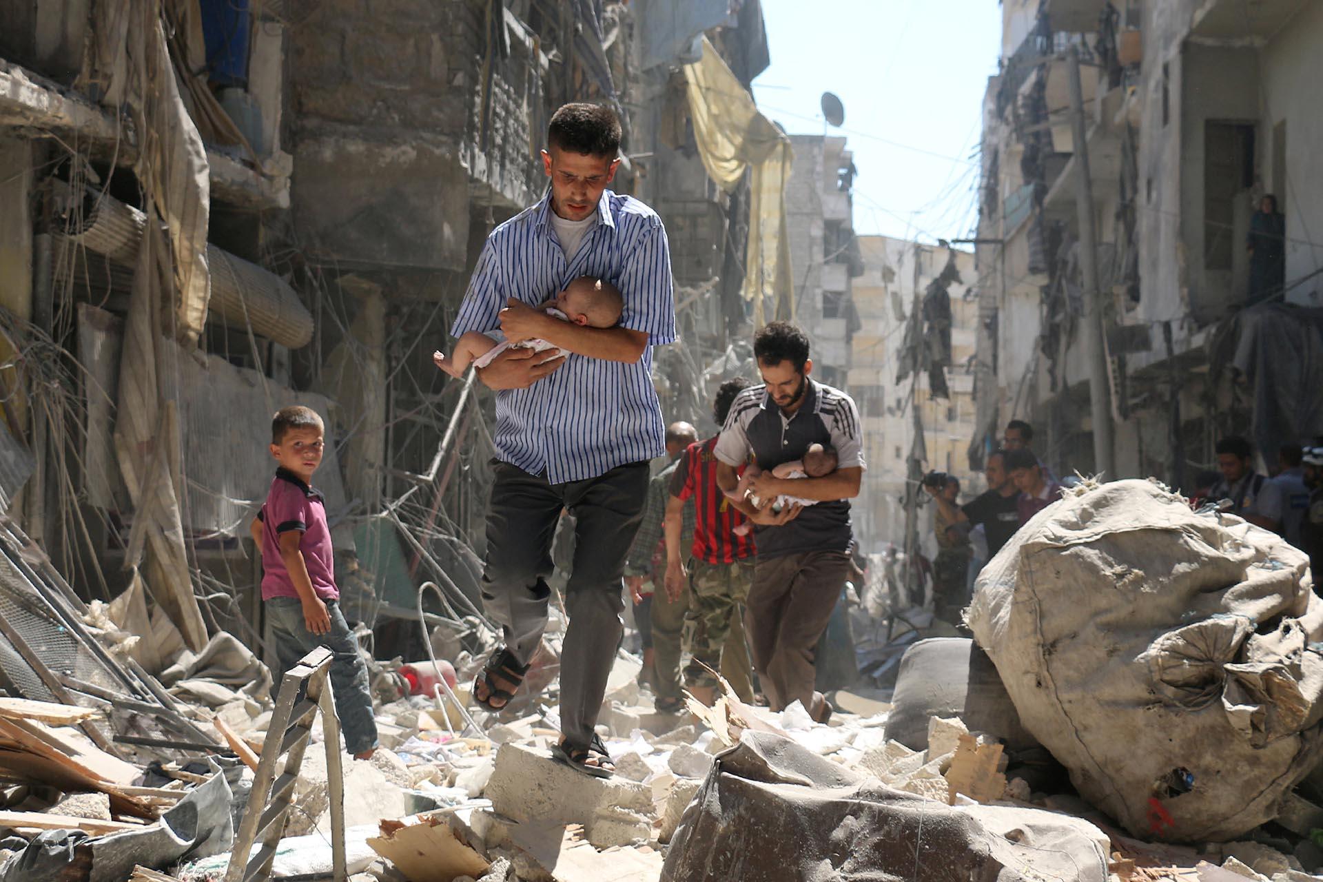 Spot News, segundo premio. Hombres sirios cargan bebés mientras se abren paso entre los escombros de edificios destruidos tras un bombardeo en Alepo, el 11 de septiembre de 2016. Ameer Alhalbi, Agence France-Presse