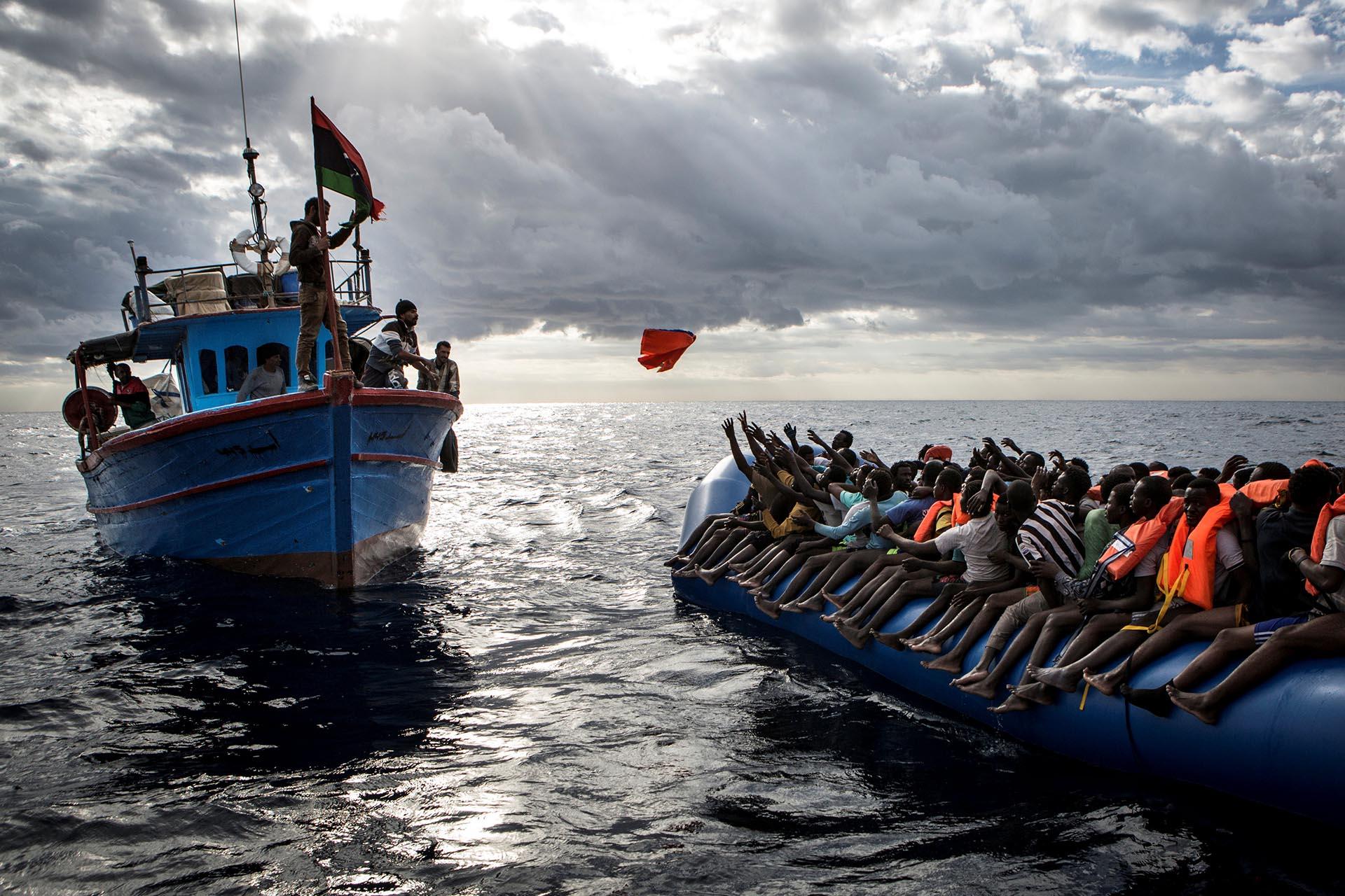 Spot News, tercer premio. Pescadores libios arrojan chalecos salvavidas a un precario bote lleno de migrantes. Mathieu Willcocks/MOAS.eu