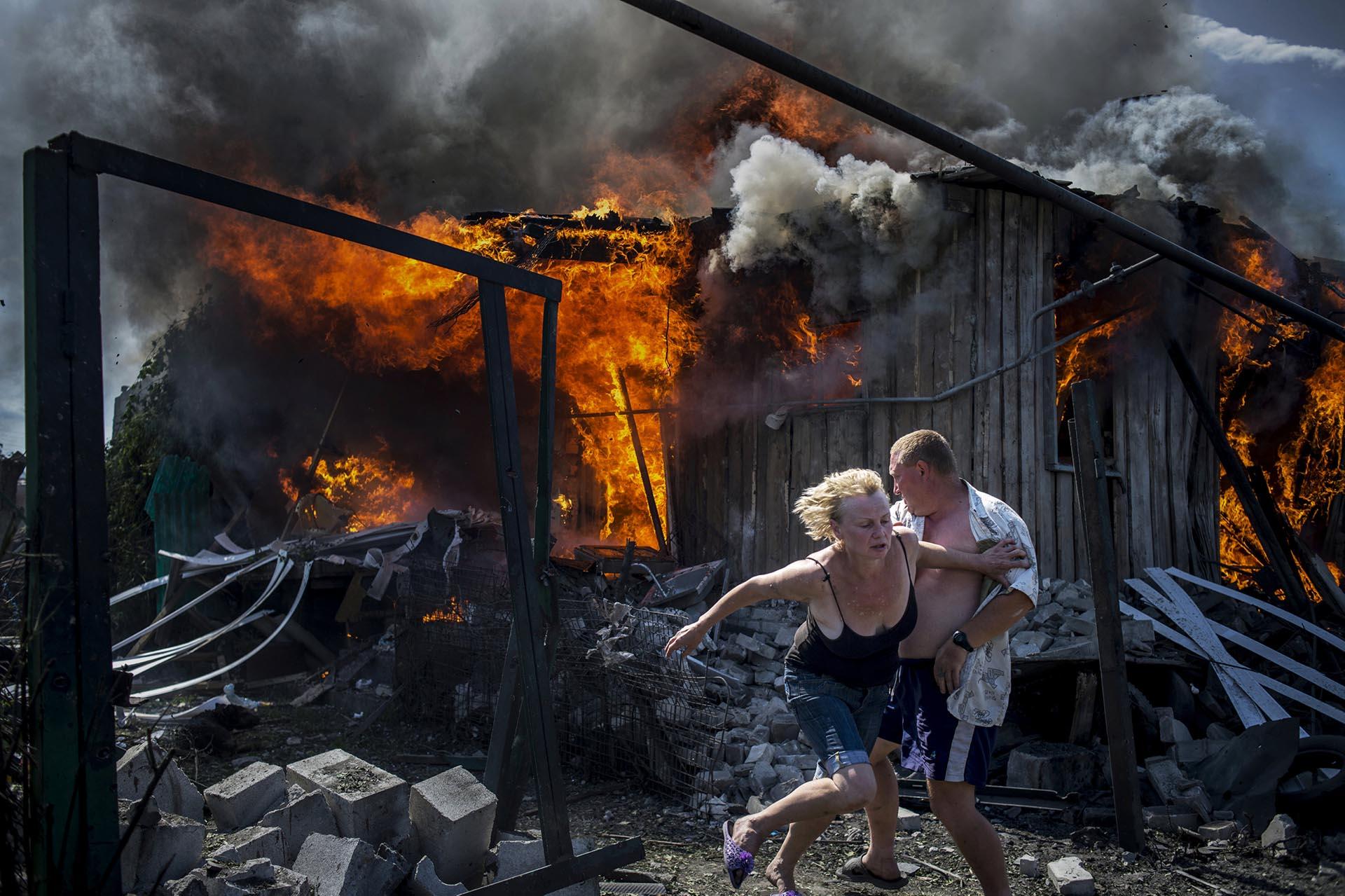 Proyectos a Largo Plazo, primer premio. Ciudadanos escapan de una casa en llamas enLuhanskaya. Rossiya Segodnya, REUTERS