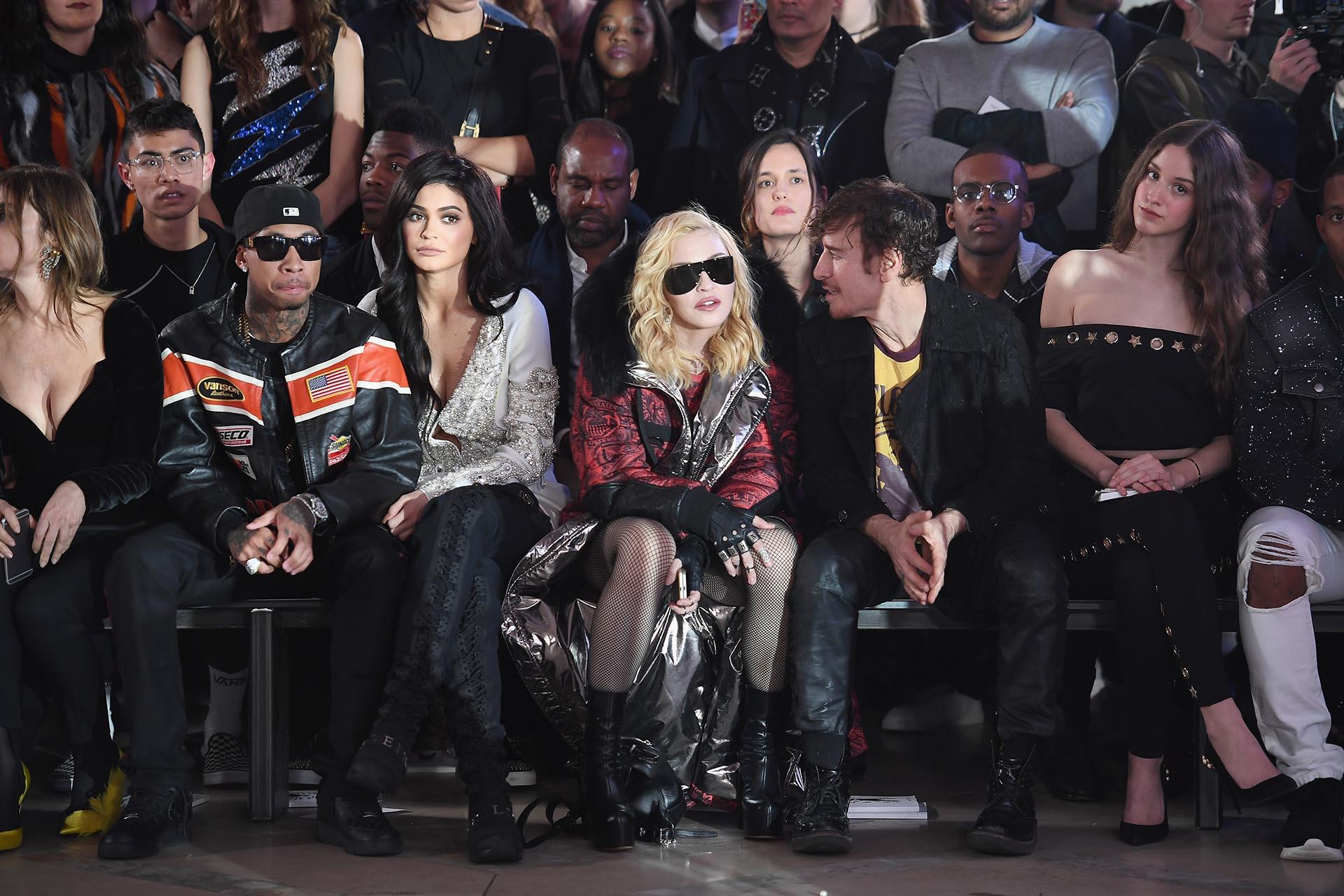 Vestida con un abrigo de capucha, medias de red, guantes, botas y grandes anteojos negros, Madonna se ubicó en la 'front row' junto a Tyga, Kylie Jenner y Steven Klein