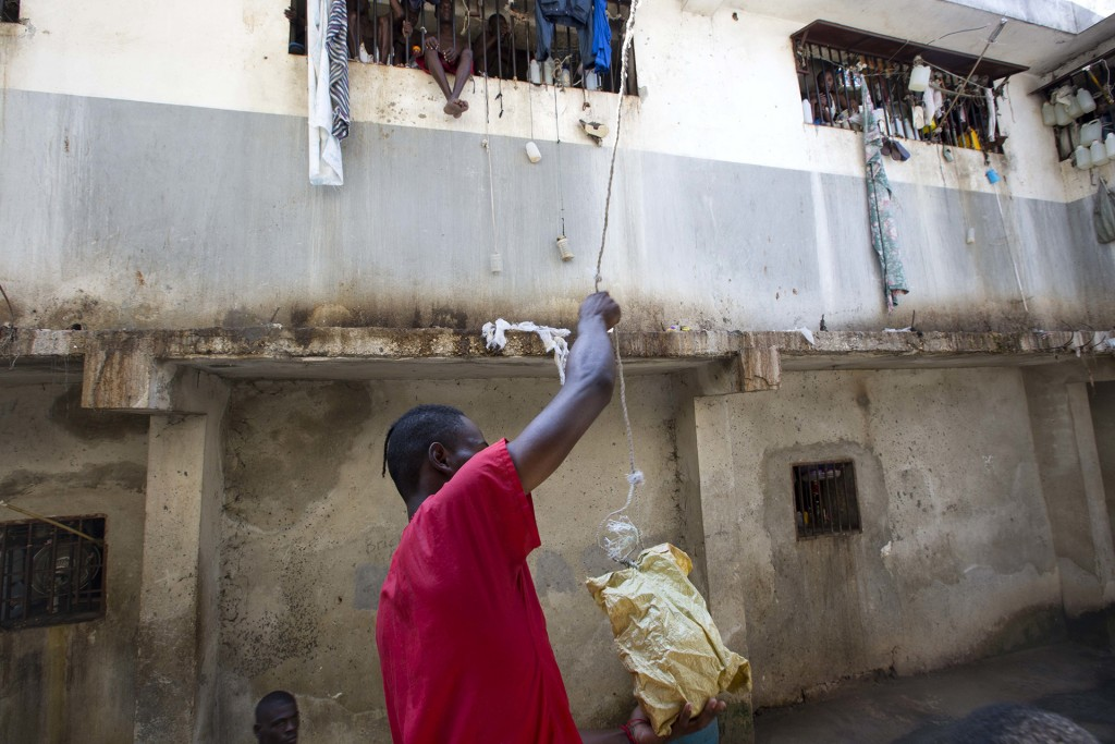 Un prisionero carga comida en una bolsa que se elevará hasta los pisos superiores de la cárcel (AP)