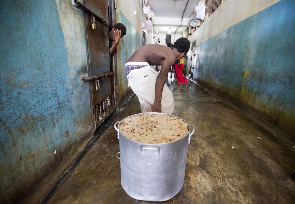 Un prisionero arrastra una olla llena con la comida que se repite todos los días: arroz y frijoles. Las autoridades de la cárcel dicen no recibir los fondos necesarios del gobierno para alimentar correctamente a todos y los casos de anemia y desnutrición abundan (AP)