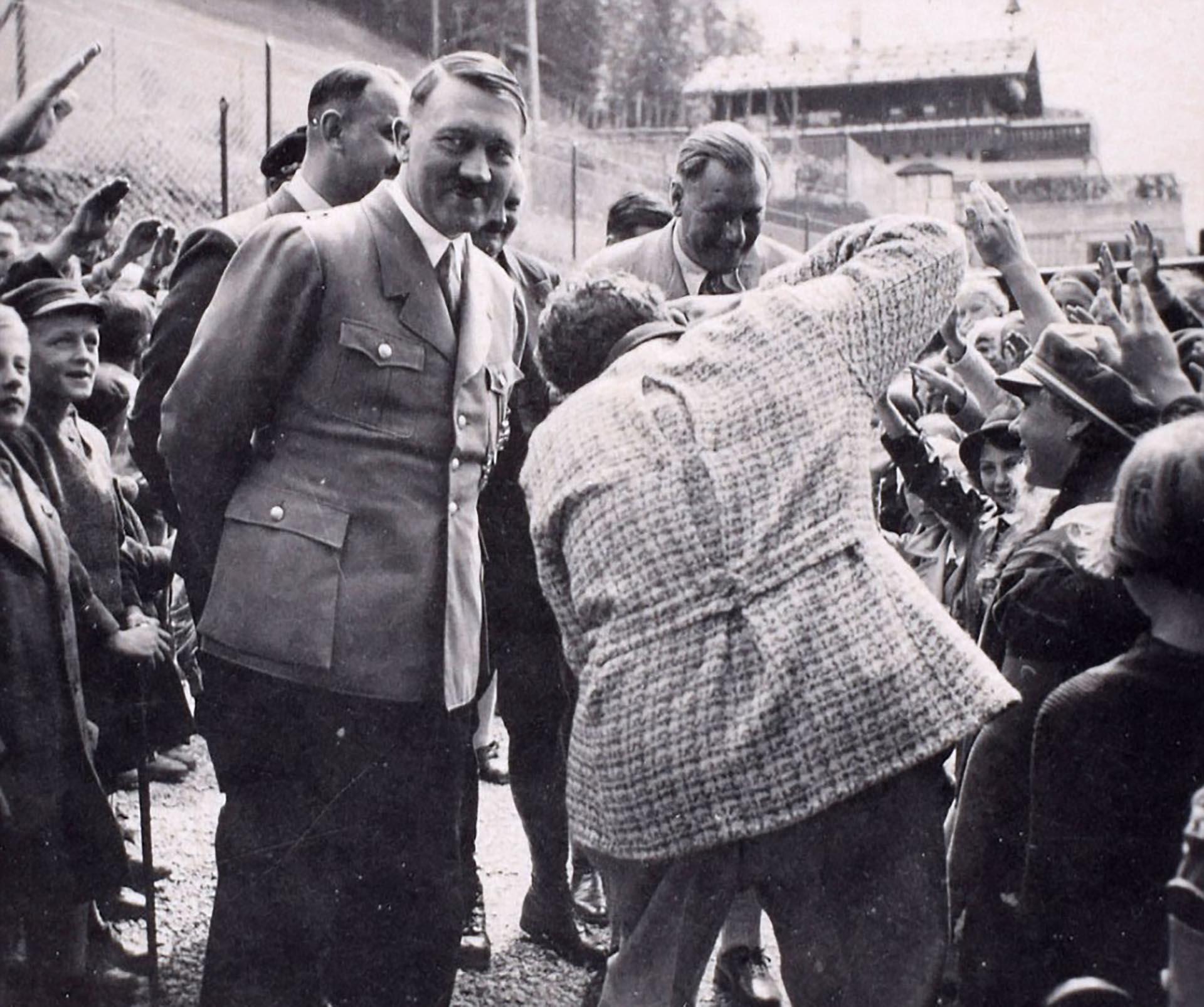 En la Bavaria, en la base de Berghof, Hitler saluda a niños. Sonriente, detrás se oculta una máquina de muerte