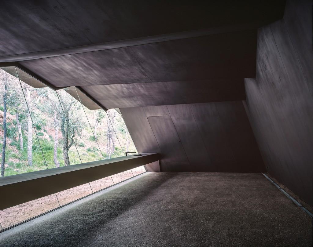 """Uno de los """"laboratorios"""" del viñedo Bell Lloc. El techo metálico con pliegues y la pared inclinada crean una gran ventana con vista al bosque, en Girona, España"""