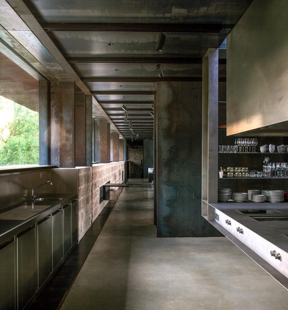 La cocina conduce a un área de exhibición y a un pequeño auditorio. La ventana ofrece vistas contínuas al paisaje verde