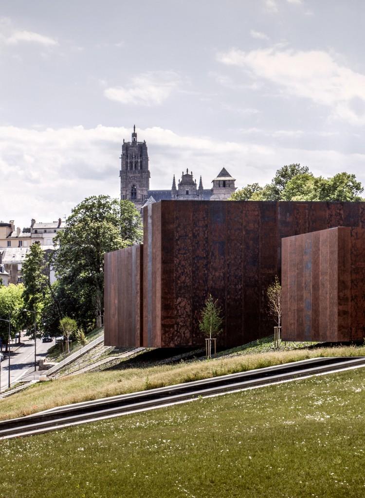Vista lateral del museo Soulages, con una apariencia similar a la de un contenedor en un camino inclinado que lleva a un parque local, lo que crea una conexión entre el área verde y la ciudad