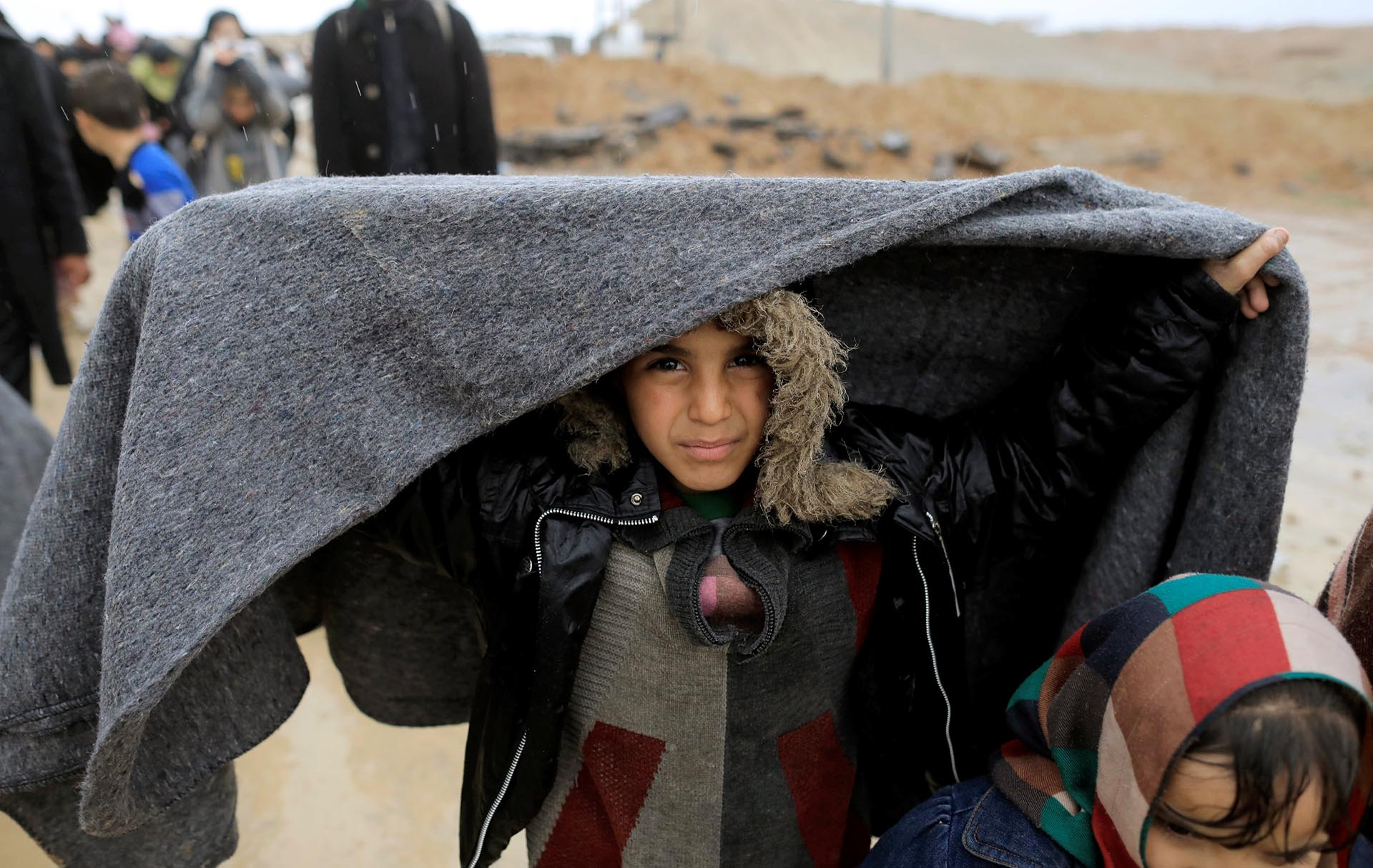 Una niña iraquí se tapa con una manta de la lluvia en plena huida