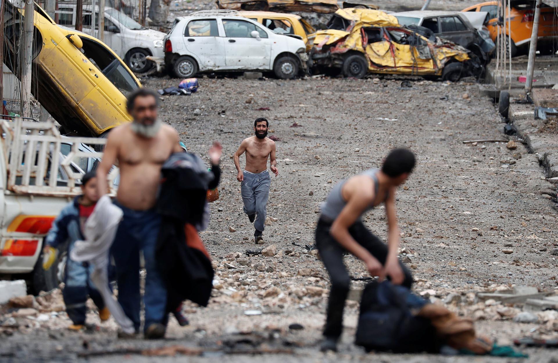 Muchos hombres huyen con el torso desnudo para mostrar que no llevan chalecos suicidas, para evitar ser confundidos con terroristas de ISIS