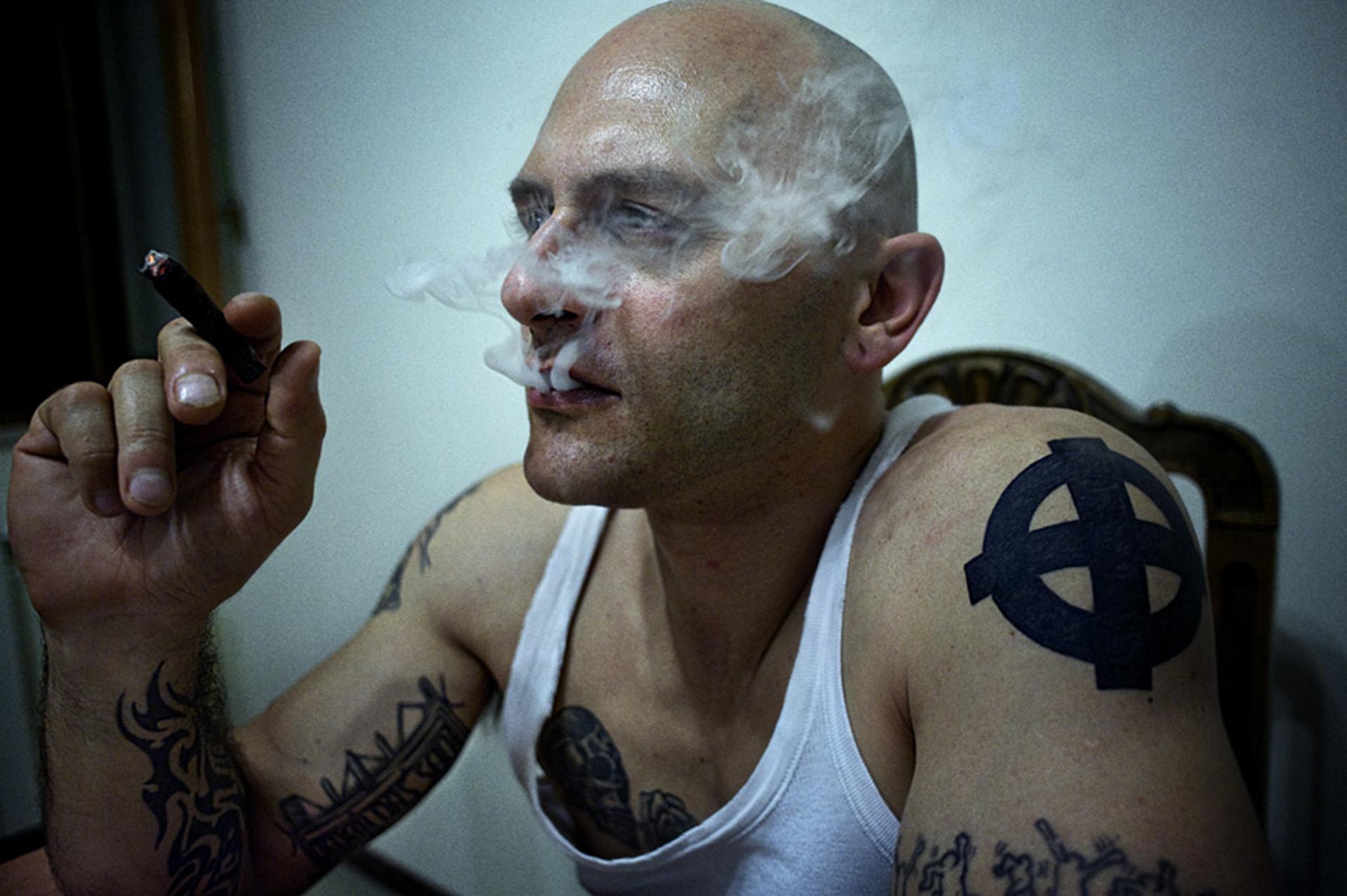 Armando, un referente de los grupos neonazis romanos, fumando un habano cubano en su casa cerca de Roma