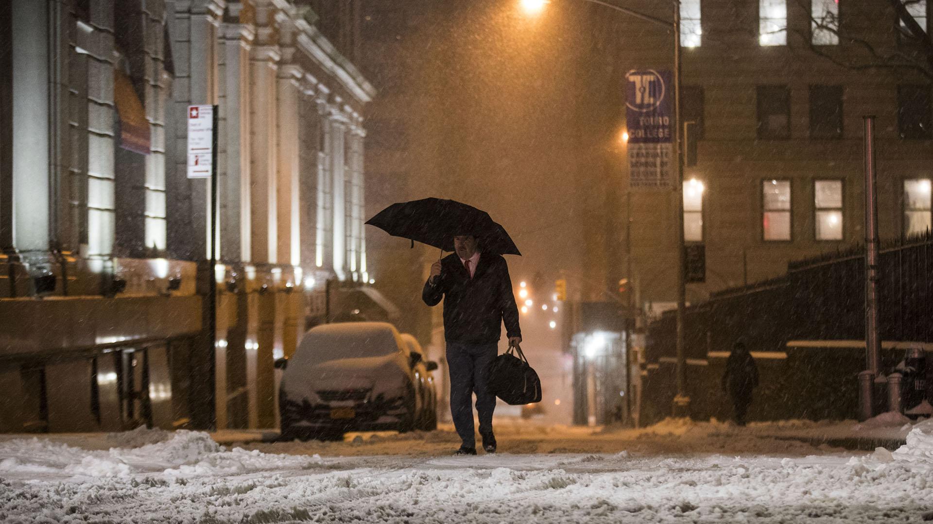 """Un hombre desafía a la tormenta y el """"estado de emergencia"""" con un paraguas"""