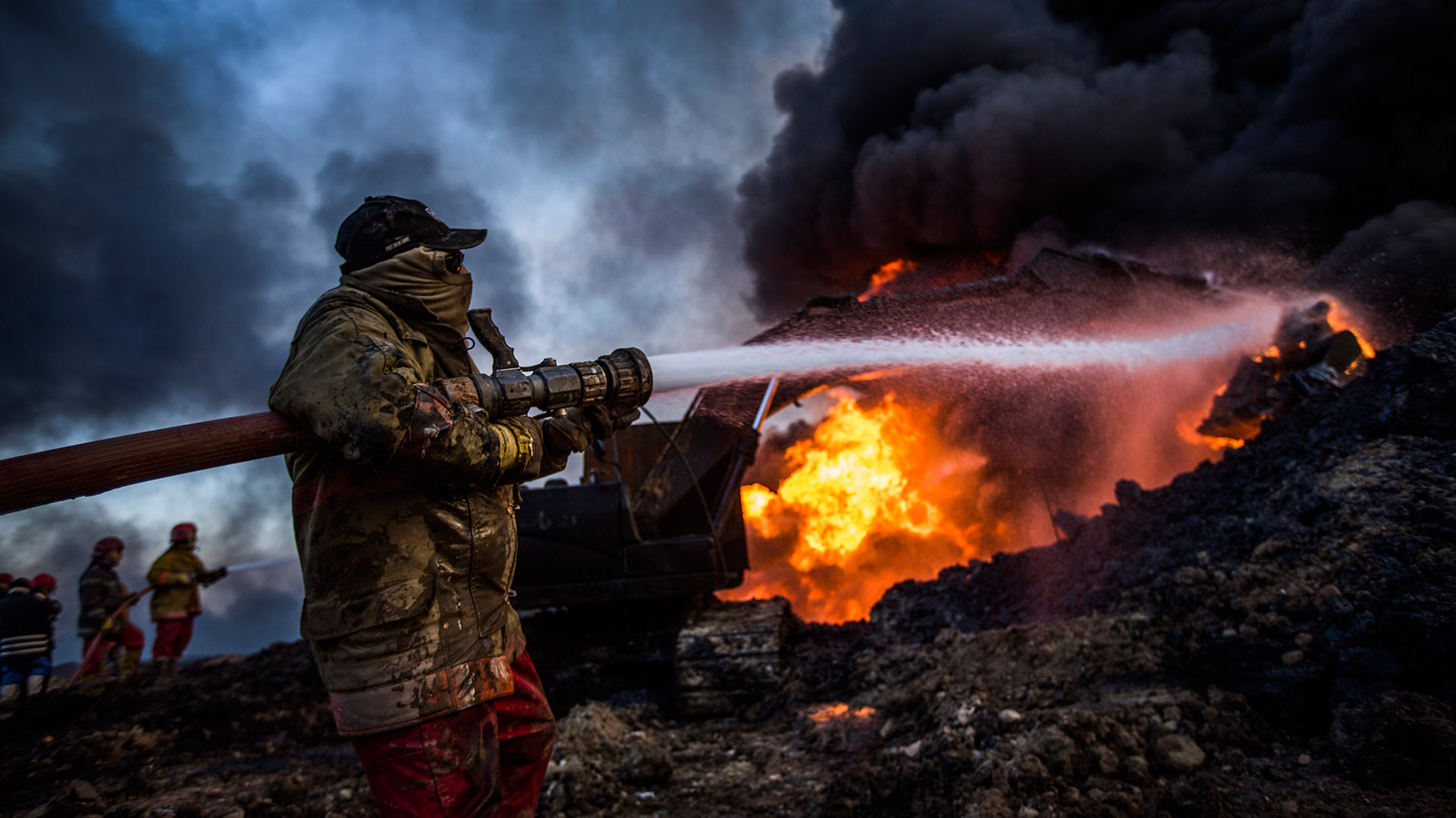 Divididos en dos equipos, los bomberos trabajan para sofocar la gran columna de fuego. Mientras la primera unidad lanza agua al interior del pozo, la segunda se encarga de refrescar la maquinaria para que no sea también pasto de las llamas. (Pablo Cobos)