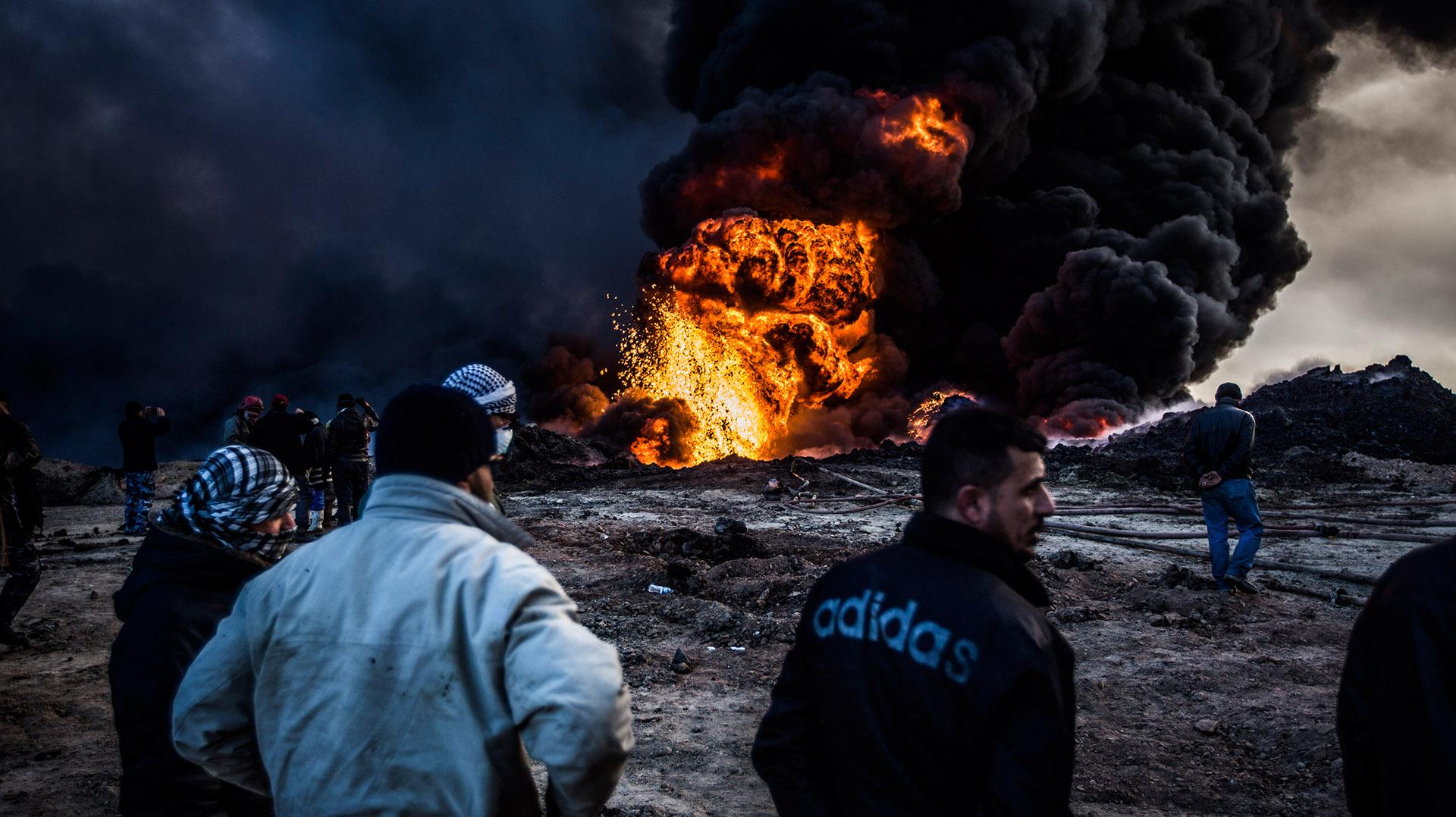 Un grupo de bomberos fuera de servicio observan el trabajo de sus compañeros desde la distancia. El calor hace imposible acercarse sin el equipo de protección. (Pablo Cobos)